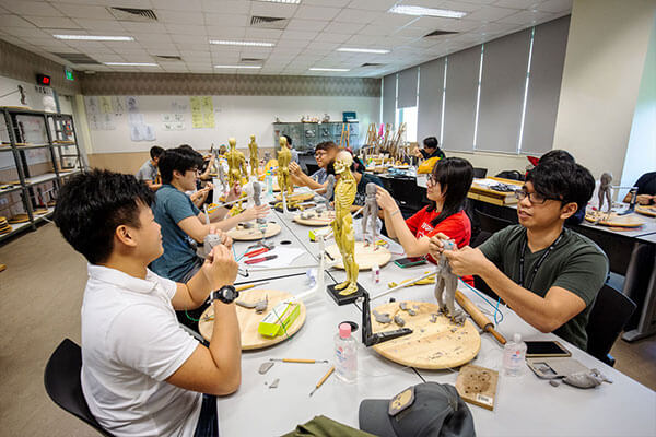 Students at a long table model human figures with gray clay based on miniature skeleton models standing between them.