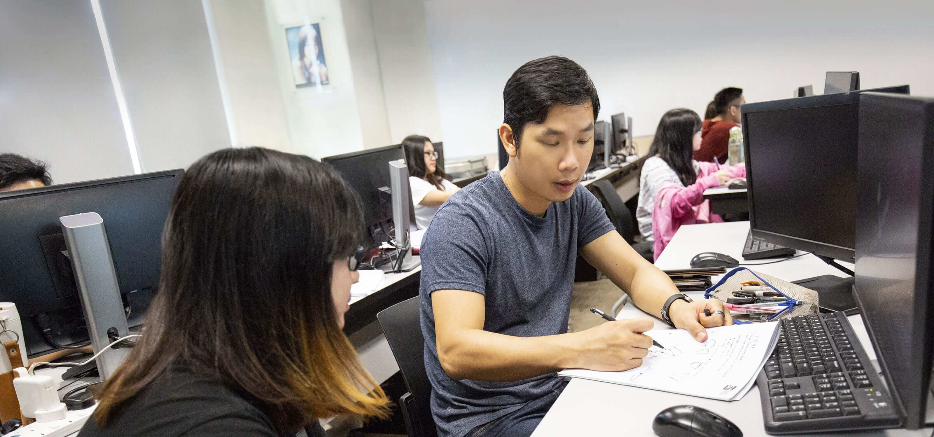 Two DigiPen (Singapore) students working together in a classroom