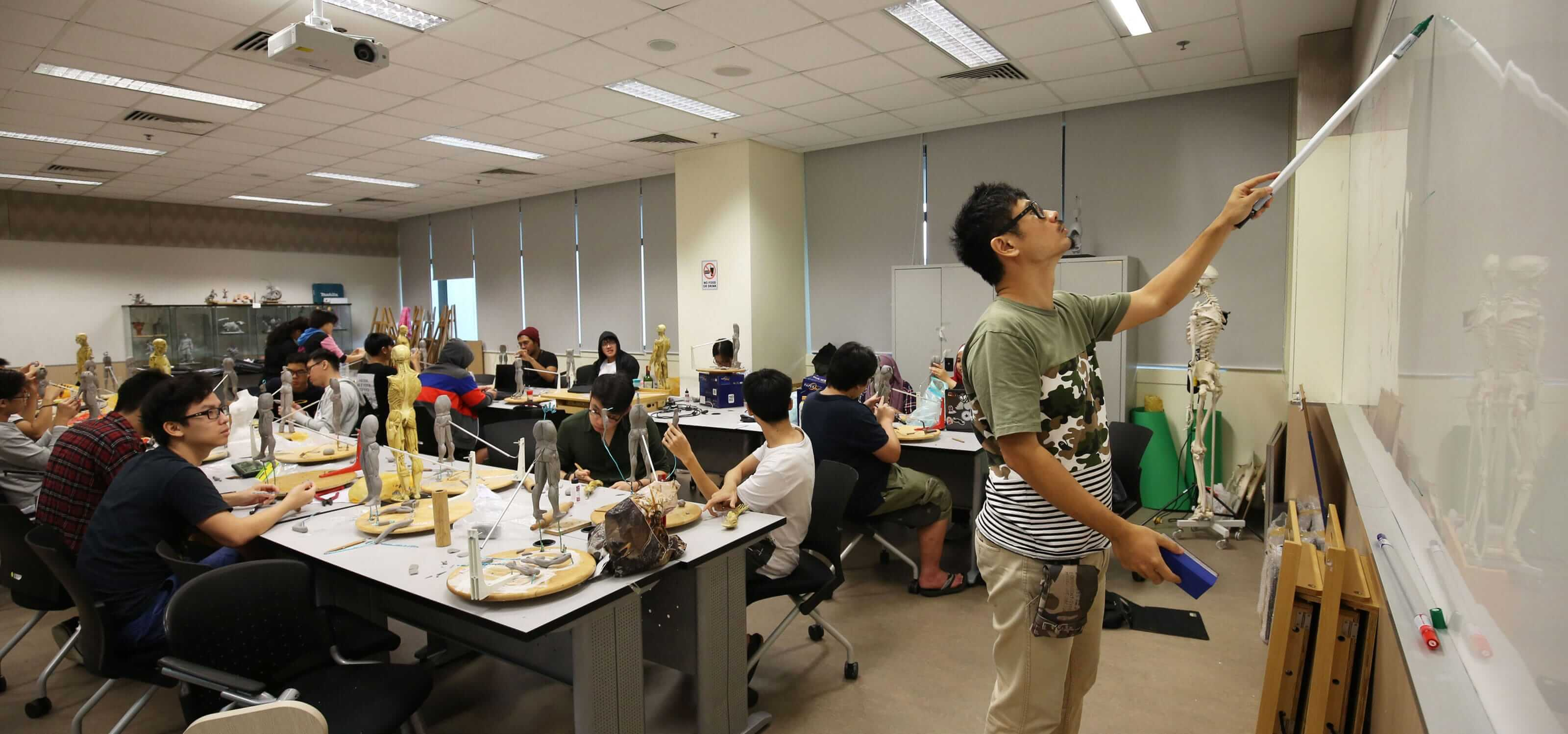 Students in a DigiPen (Singapore) sculpting class watch as an instructor writes on a whiteboard
