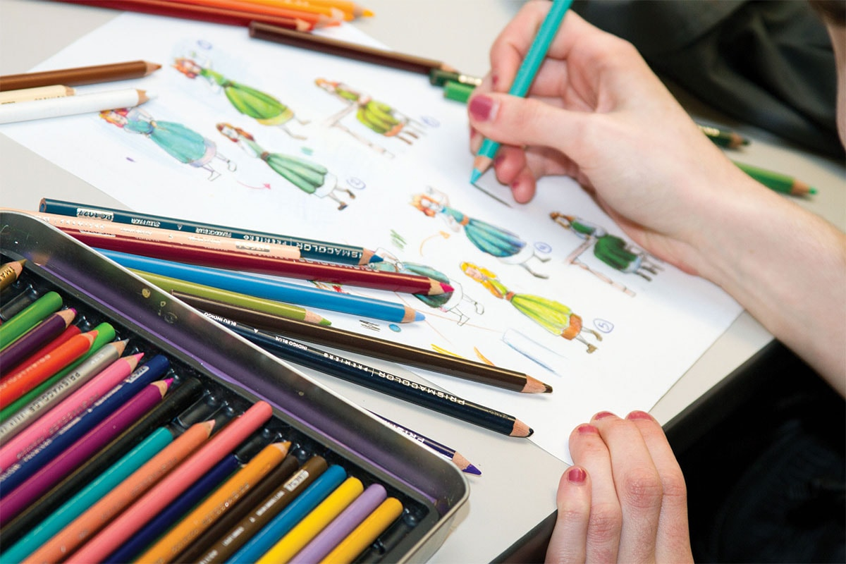Close-up view of a DigiPen student sketching various female characters with colored pencils in the foreground