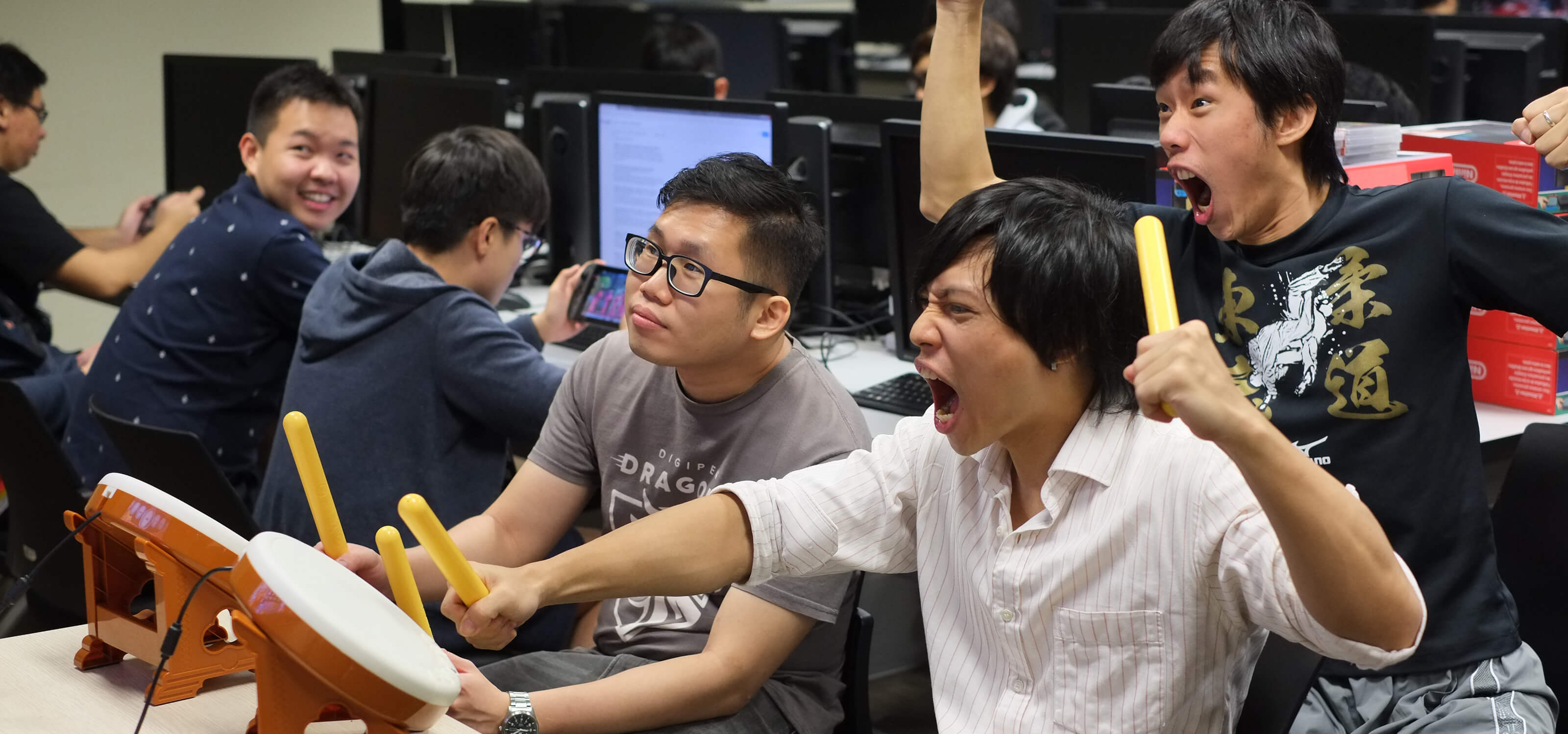 Students use yellow drumsticks to hammer away on a drum-type video game controller as others watch excitedly behind.