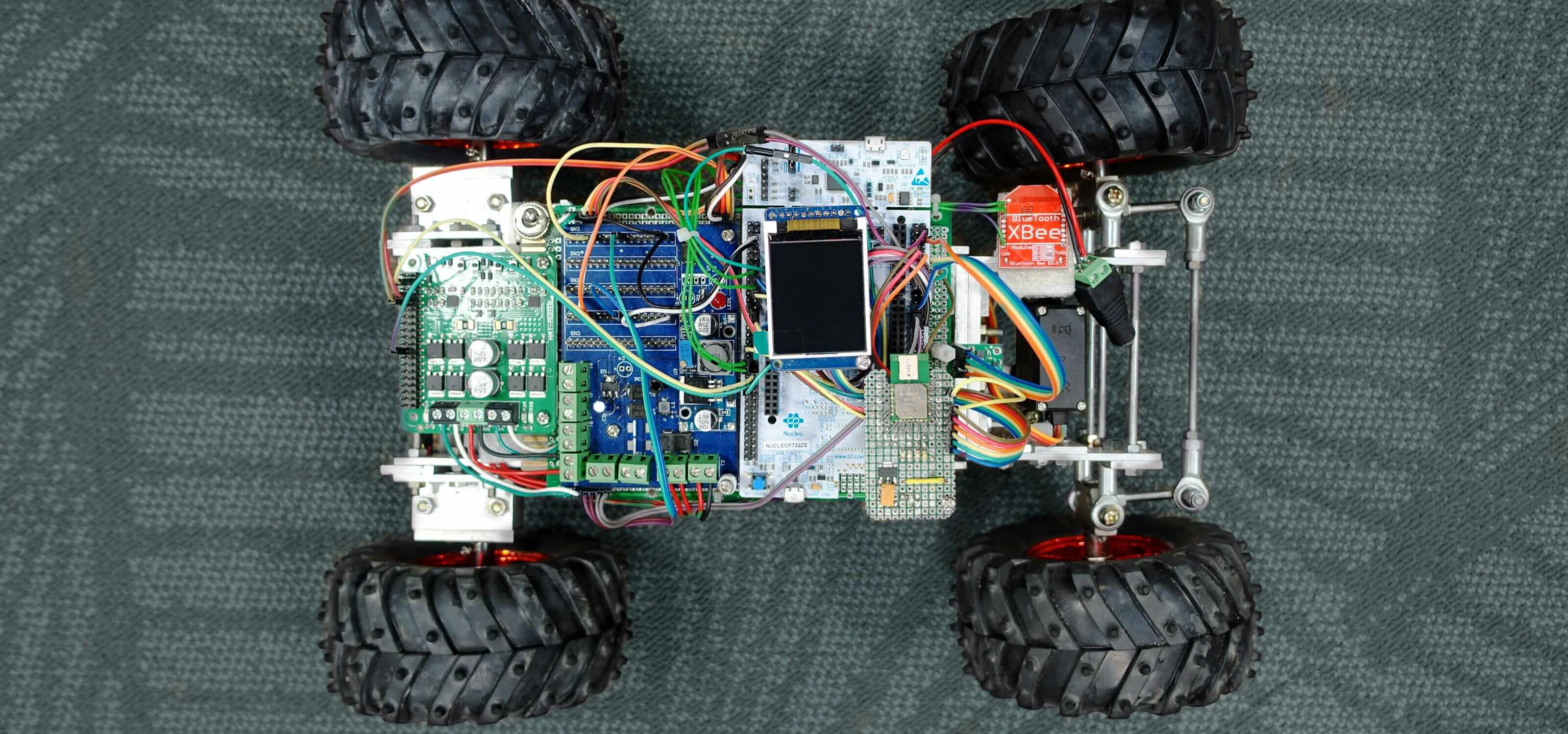 A model racing car seen from above with textured black tires and colorful exposed wiring and circuit board.