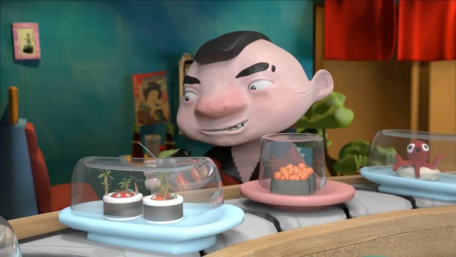 A short man with a mohawk haircut sits behind a sushi conveyor belt with playes of inventive creations under glass.
