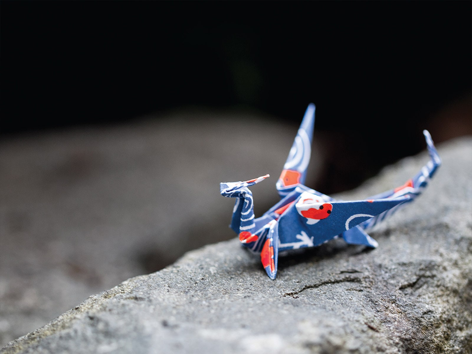 A dragon crafted from blue origami paper sitting on a rock