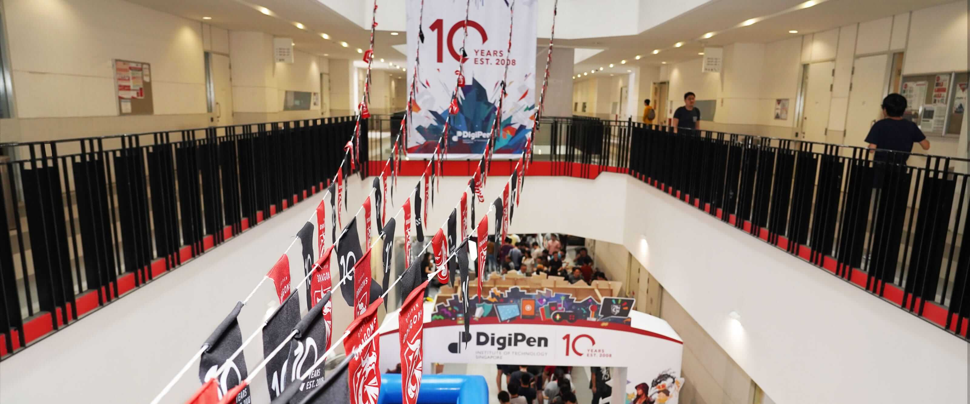 School banners and pennants hang in a multi-level, interior atrium area while a celebration takes place on the ground floor.