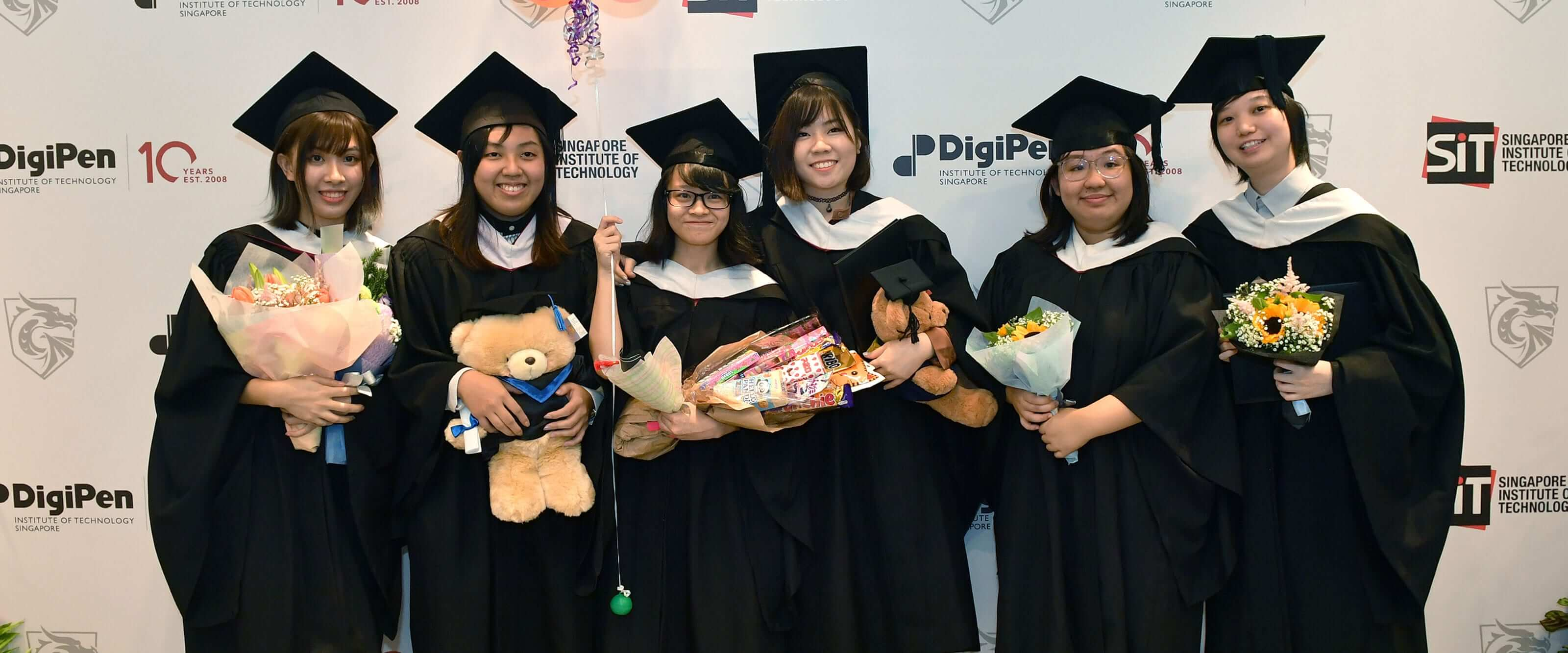 Recent college graduates in black graduation gowns and mortarboards pose for a photo holding flowers and stuffed animals.