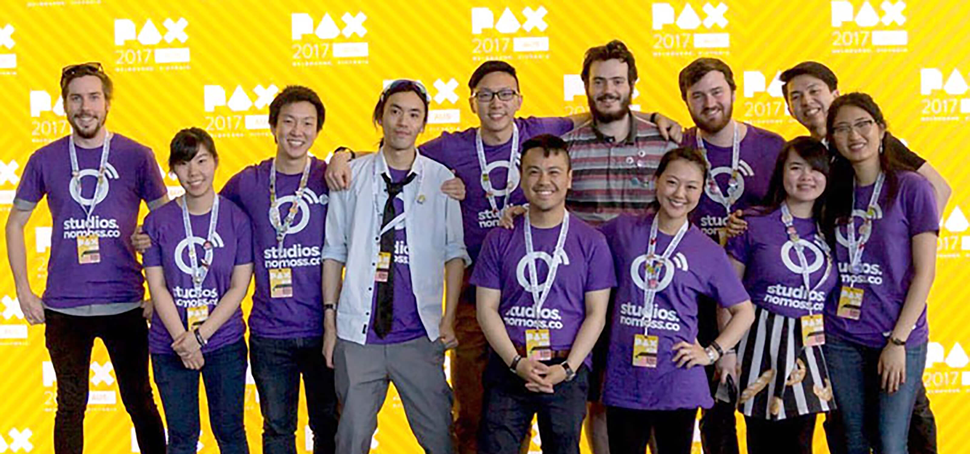 DigiPen (Sinagpore) alumnus Chen Zhiming poses with No Moss Co coworkers in front of a PAX 2017 step-and-repeat