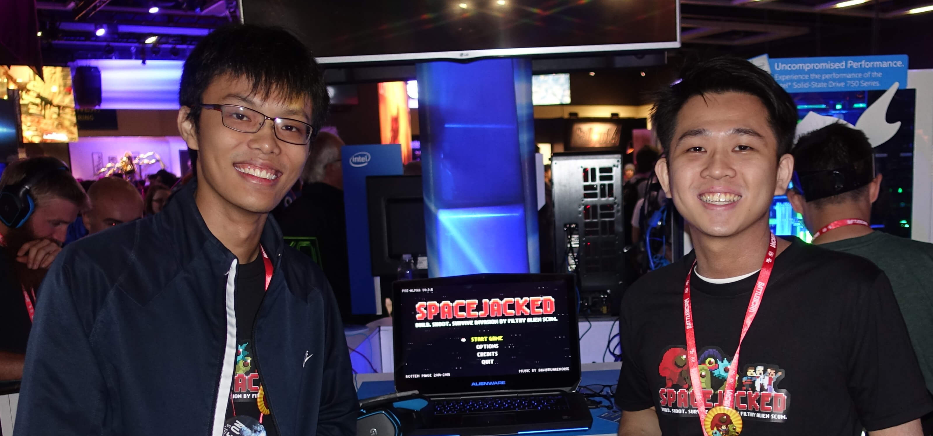 DigiPen (Singapore) graduates Chin Yong Kian and Lim Chian Song stand next to a demo of their game, Spacejacked.