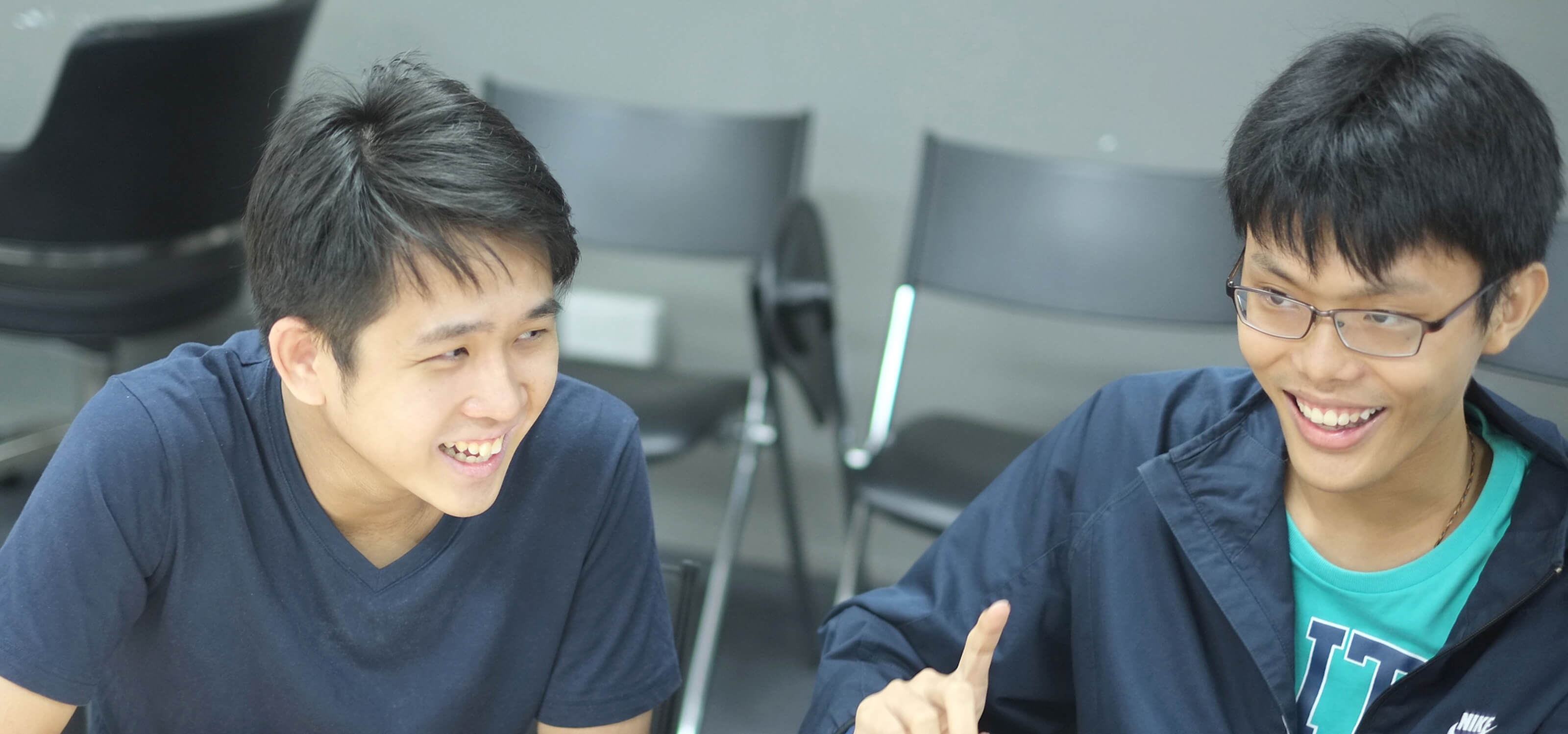 Graduates Chin Yong Kian and Lim Chian Song sit at a desk laughing