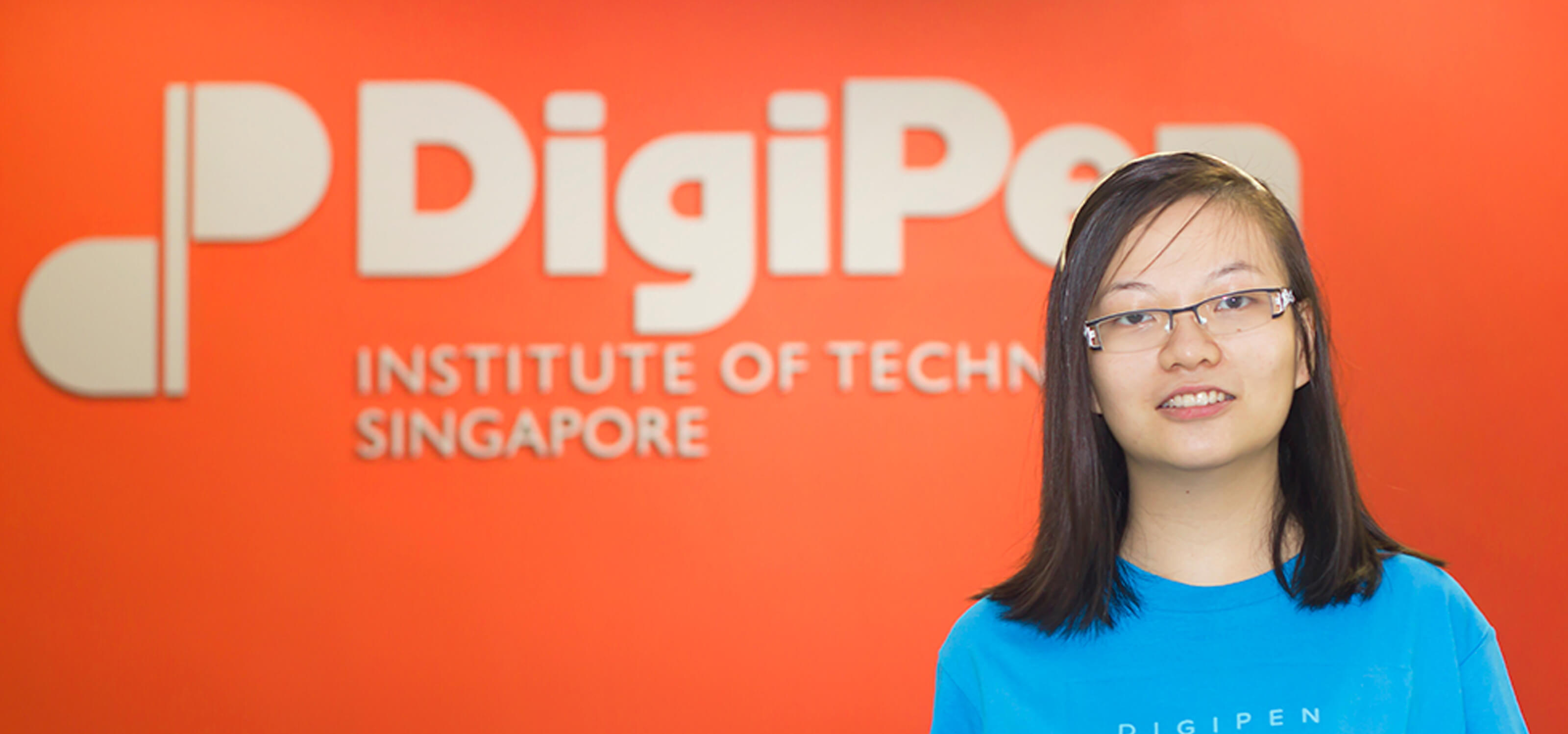 Alumna Chua Fen Ru Jurene posing for a photo in neon blue DigiPen Dragons t-shirt