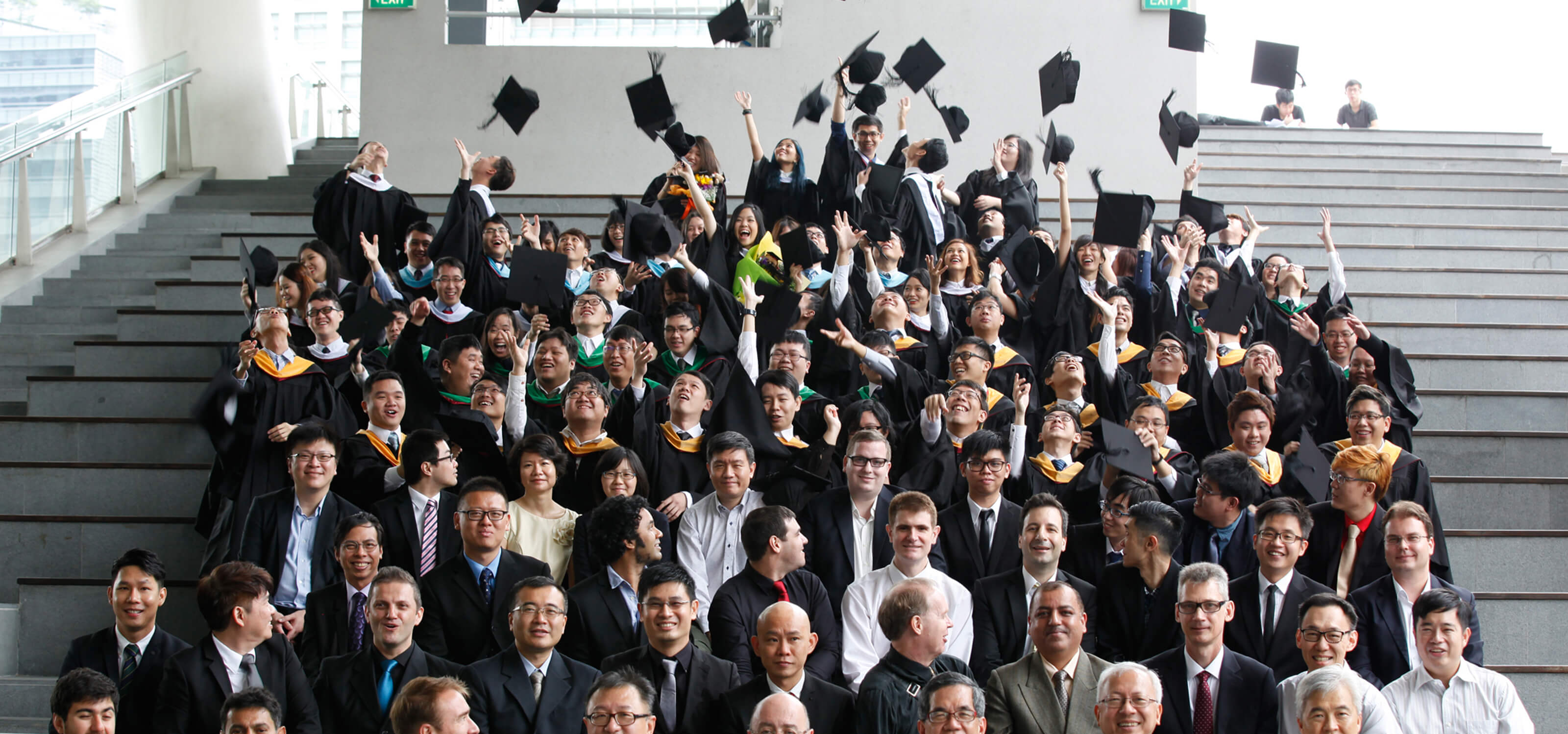 Dozens of newly graduated DigiPen alumni toss their caps in the air as faculty sits below them in bleacher seating