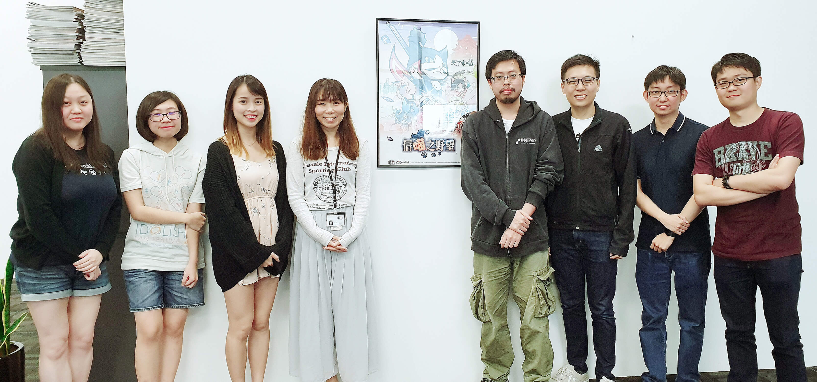 Group photo of the 8 DigiPen (Singapore) alumni who worked on Koei Tecmo's Nyapuri standing in office by a poster of the game.