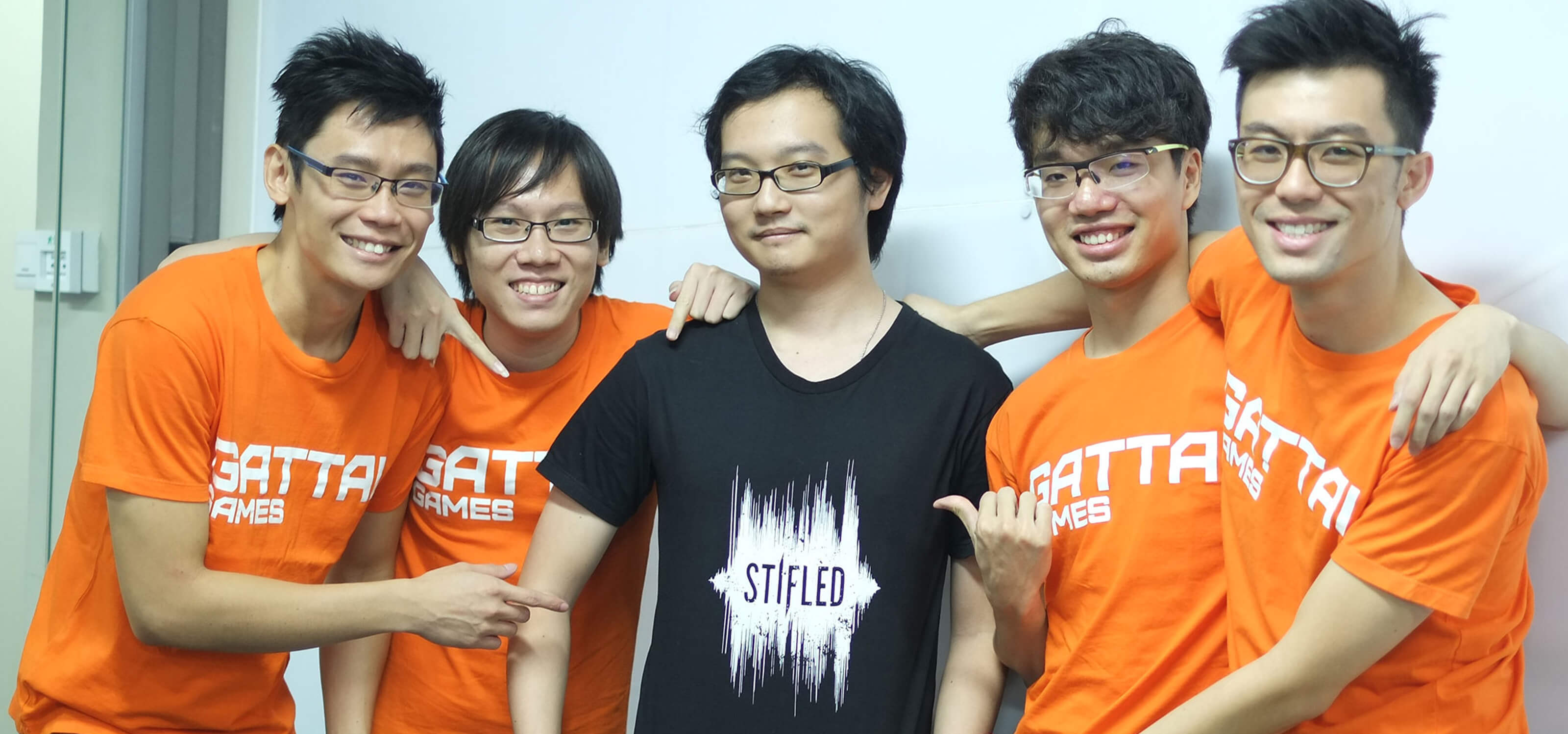 "Five members of the Stifled dev team, four in orange t-shirts reading ""Gattai Games,"" and one in a black t-shirt"