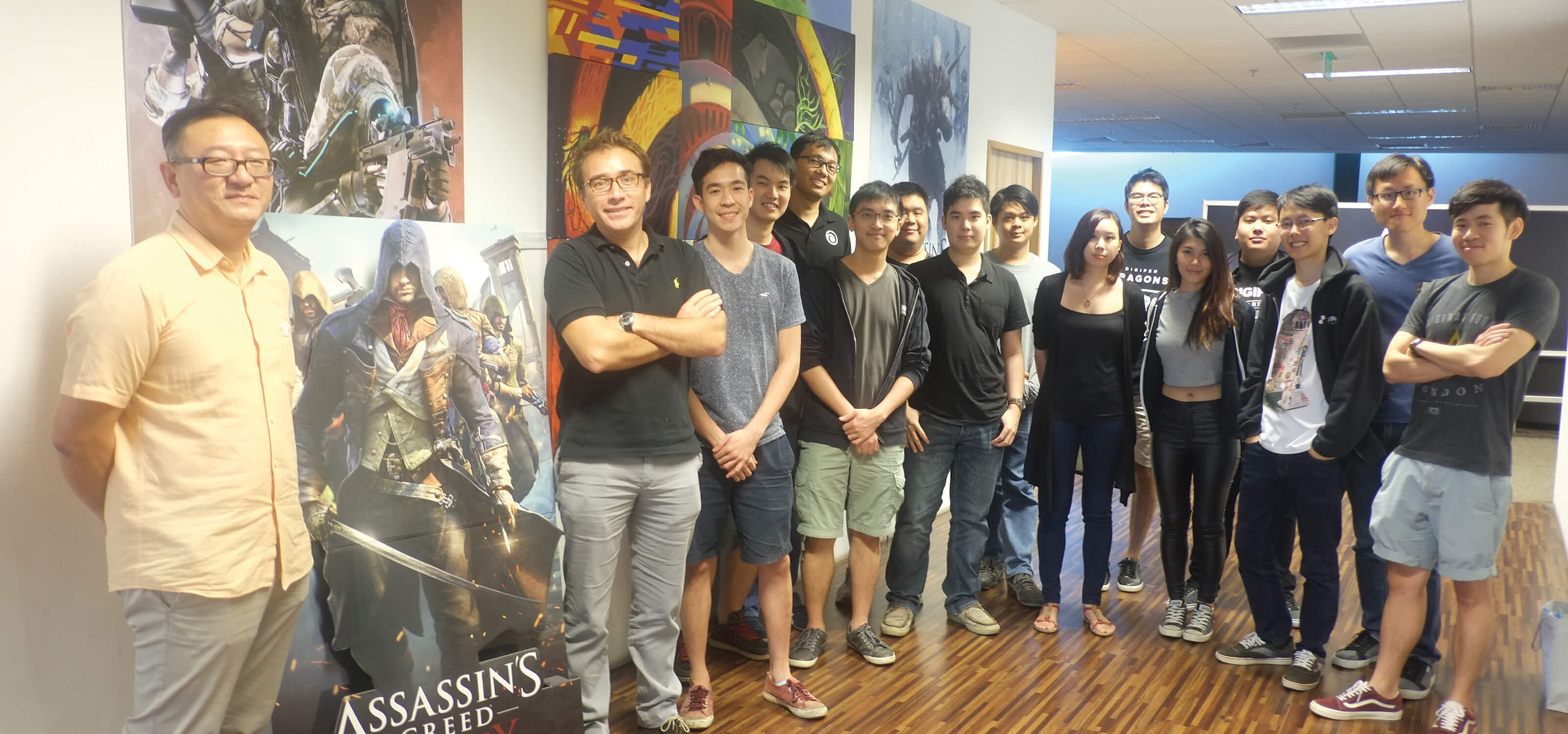 DigiPen students stand in lobby of Ubisoft Singapore office next to a cardboard cutout of an Assassin's Unity character