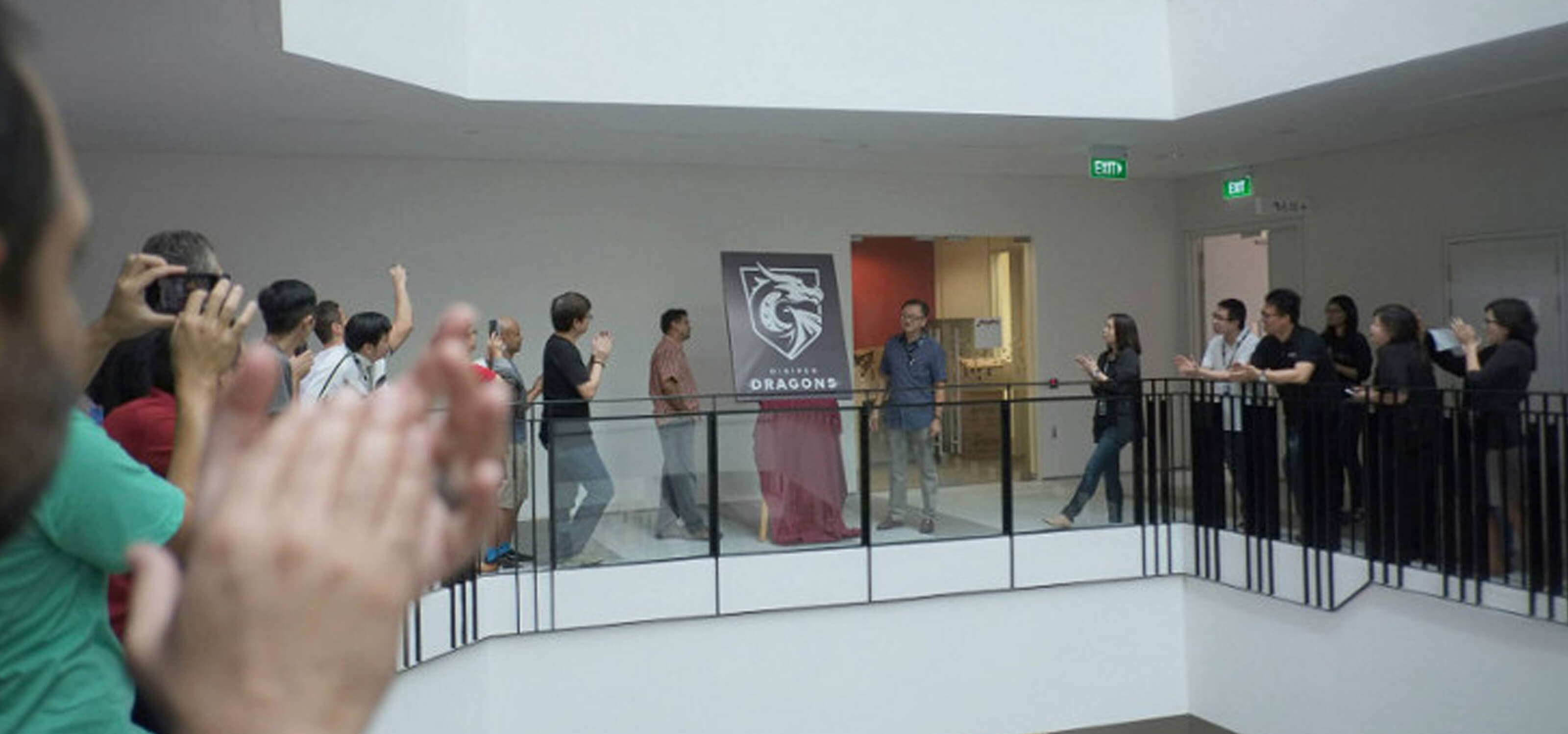 People on the second floor applaud the unveiling of a poster depicting the DigiPen Dragons logo