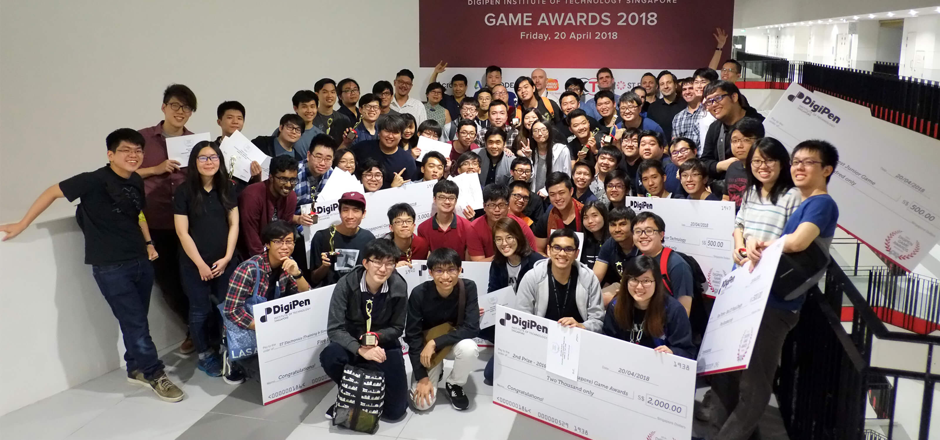 Participants in the DigiPen (Singapore) Game and Animation Awards pose, with award-winners holding giant novelty checks up front
