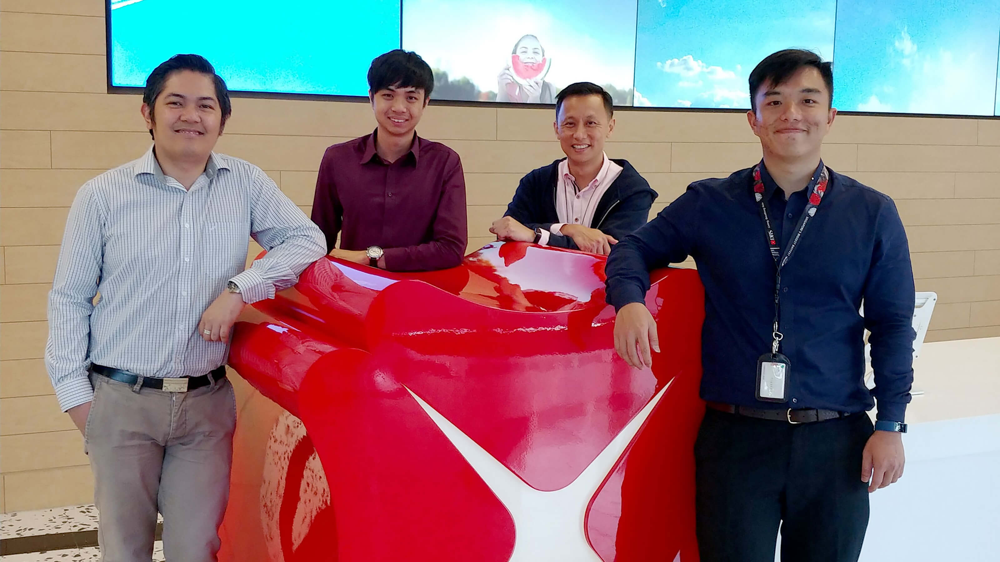 DigiPen (Singapore) alumni izaak Foong and Farris Chua pose with co-workers in DBS Bank lobby