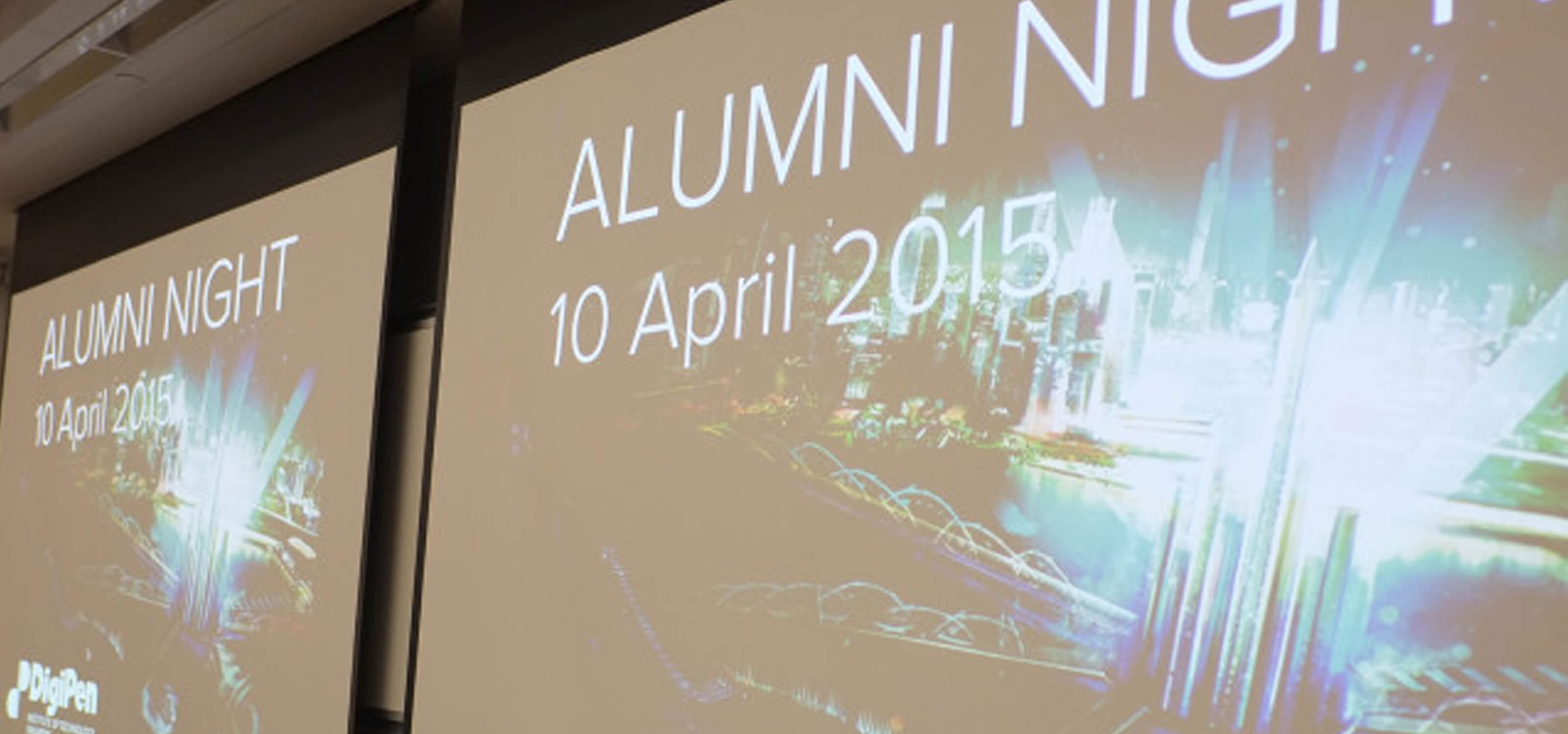 "A projection screen displays ""Alumni Night, 10 April 2015"" and a graphic of a shining futuristic city"