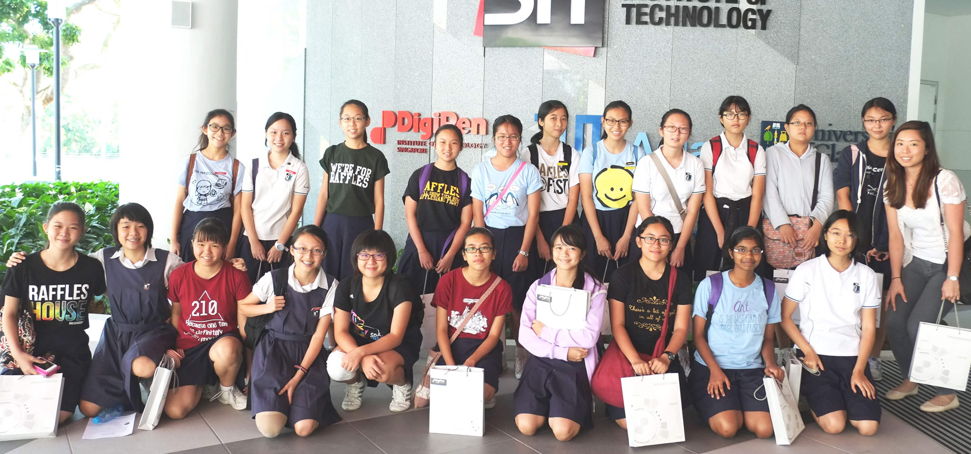A group of schoolchildren pose for a picture in front of a building displaying the Singapore Institute of Technology logo