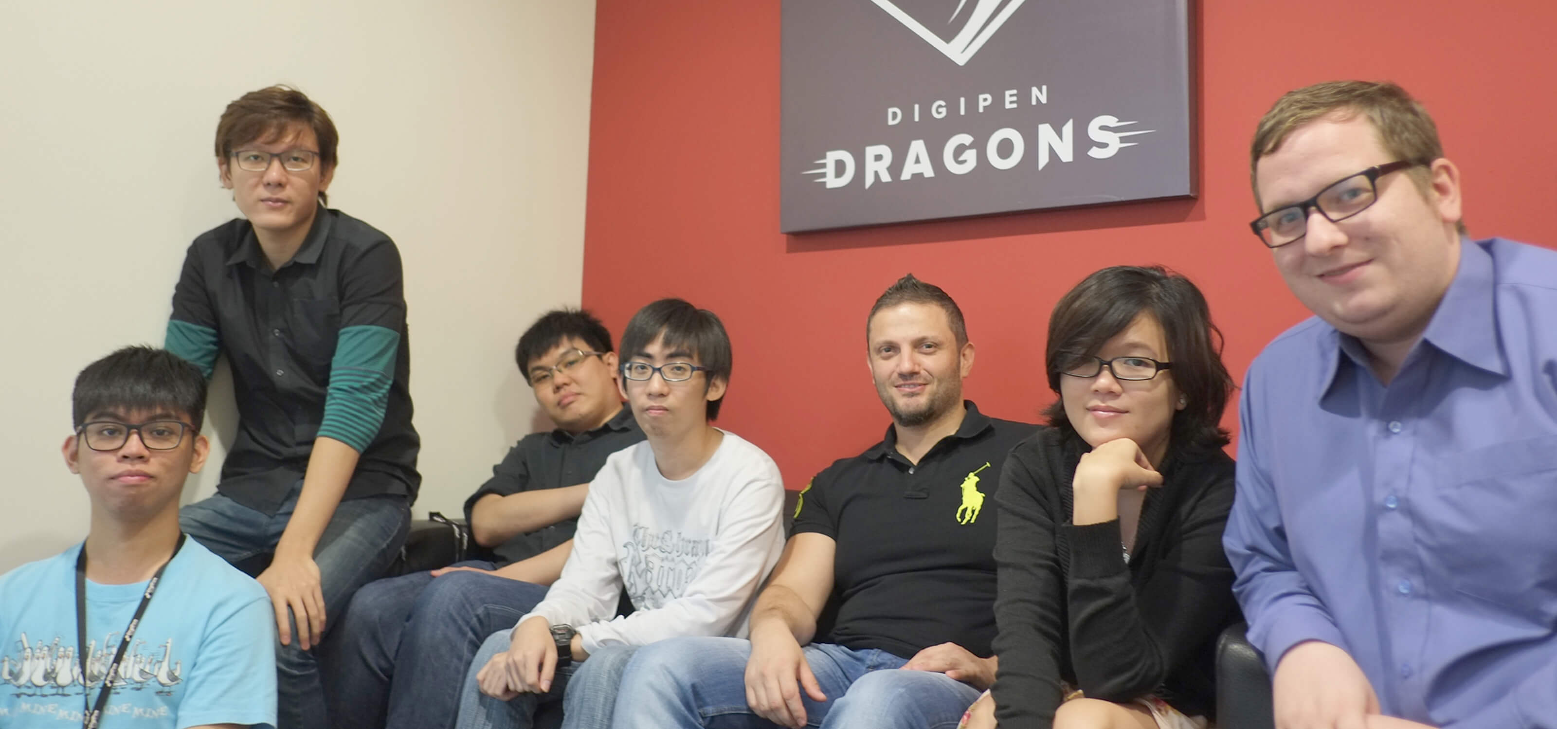 Members of the DigiPen (Singapore) Research and Development team sit at a couch below a poster of the DigiPen Dragons logo