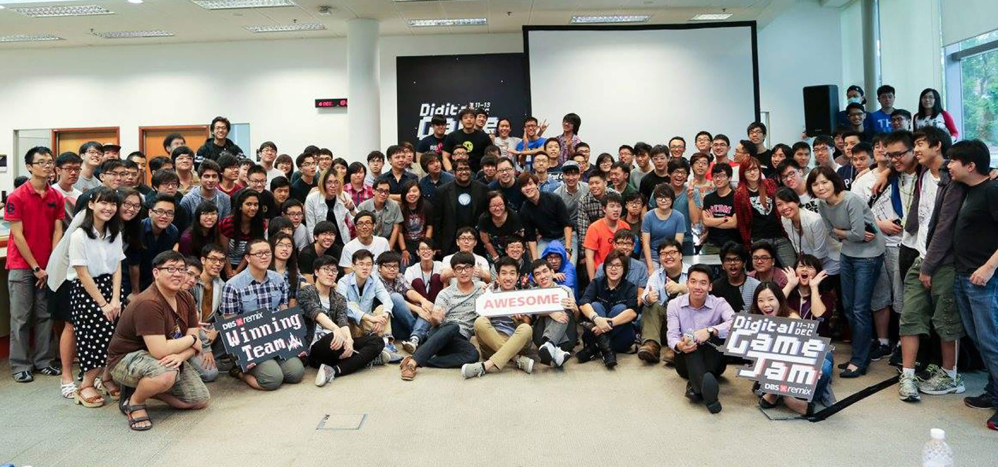 Dozens of students pose for a picture in an open, well-lit room; some hold Game Jam-related signs