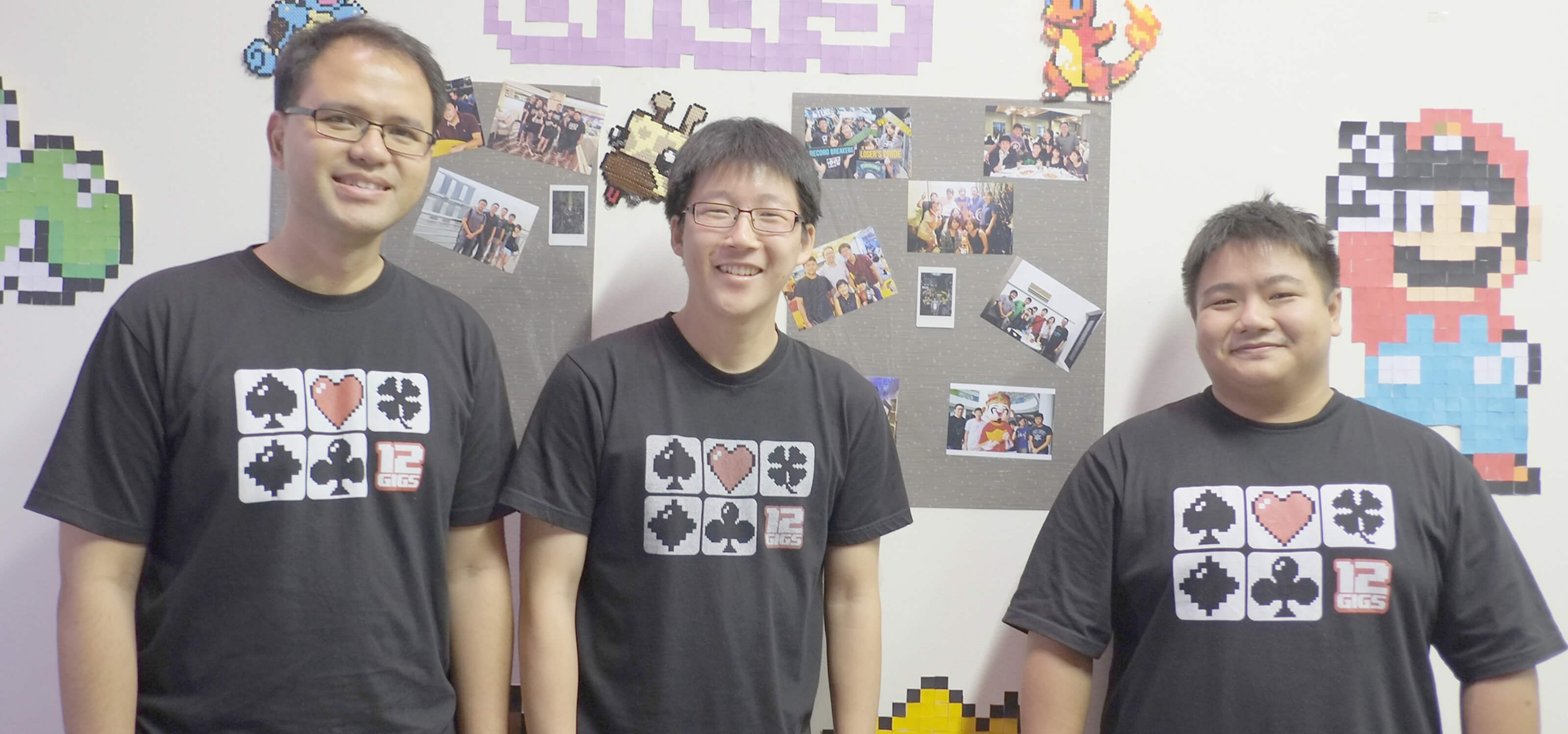 Three DigiPen graduates stand in front of a wall decorated with pixel art and the 12 Gigs logo wearing black t-shirts