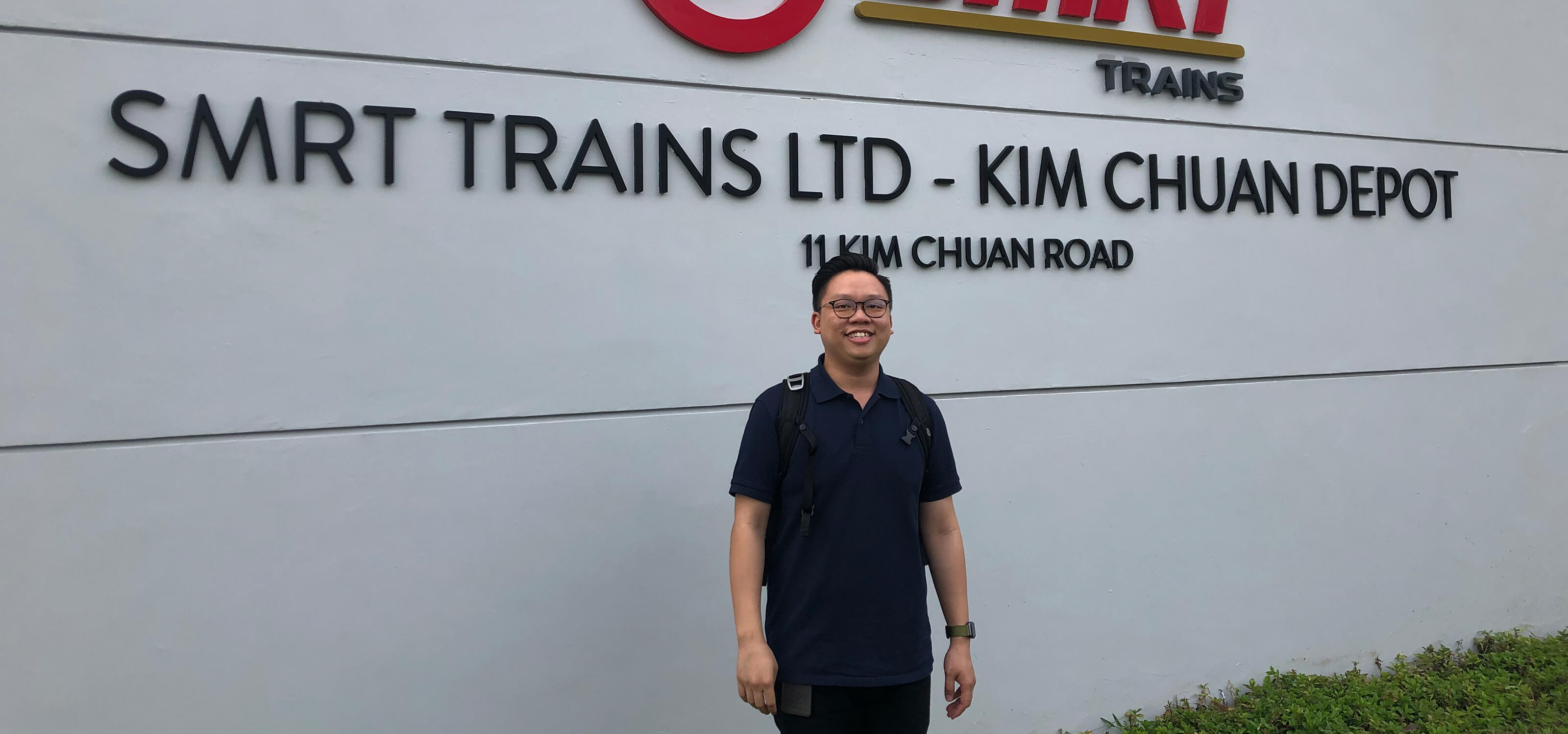 "Samuel Tan stands in front of the 'SMRT Trains Ltd. - Kim Chuan Depot"" sign."