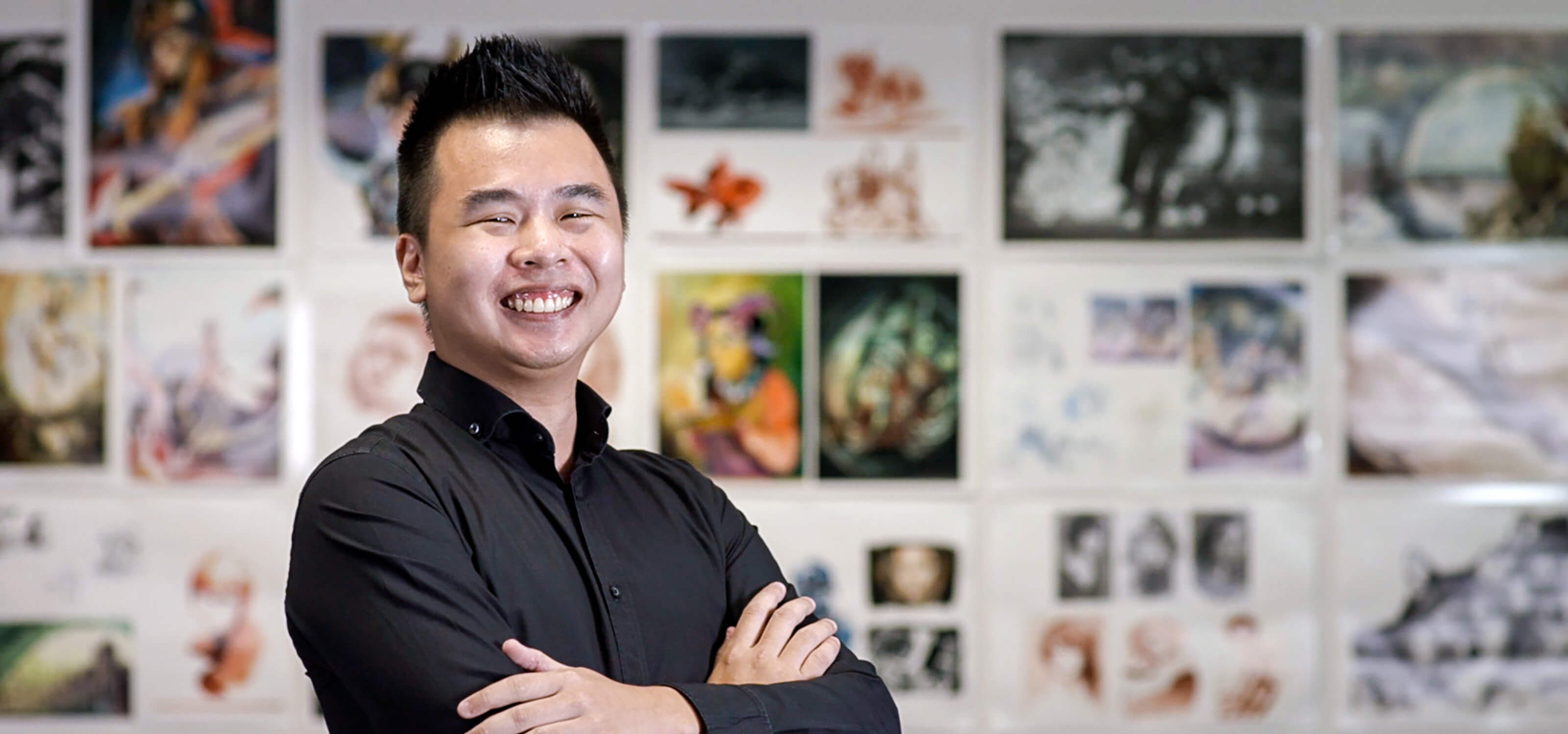 Joshua Ang stands in front of a colorful wall