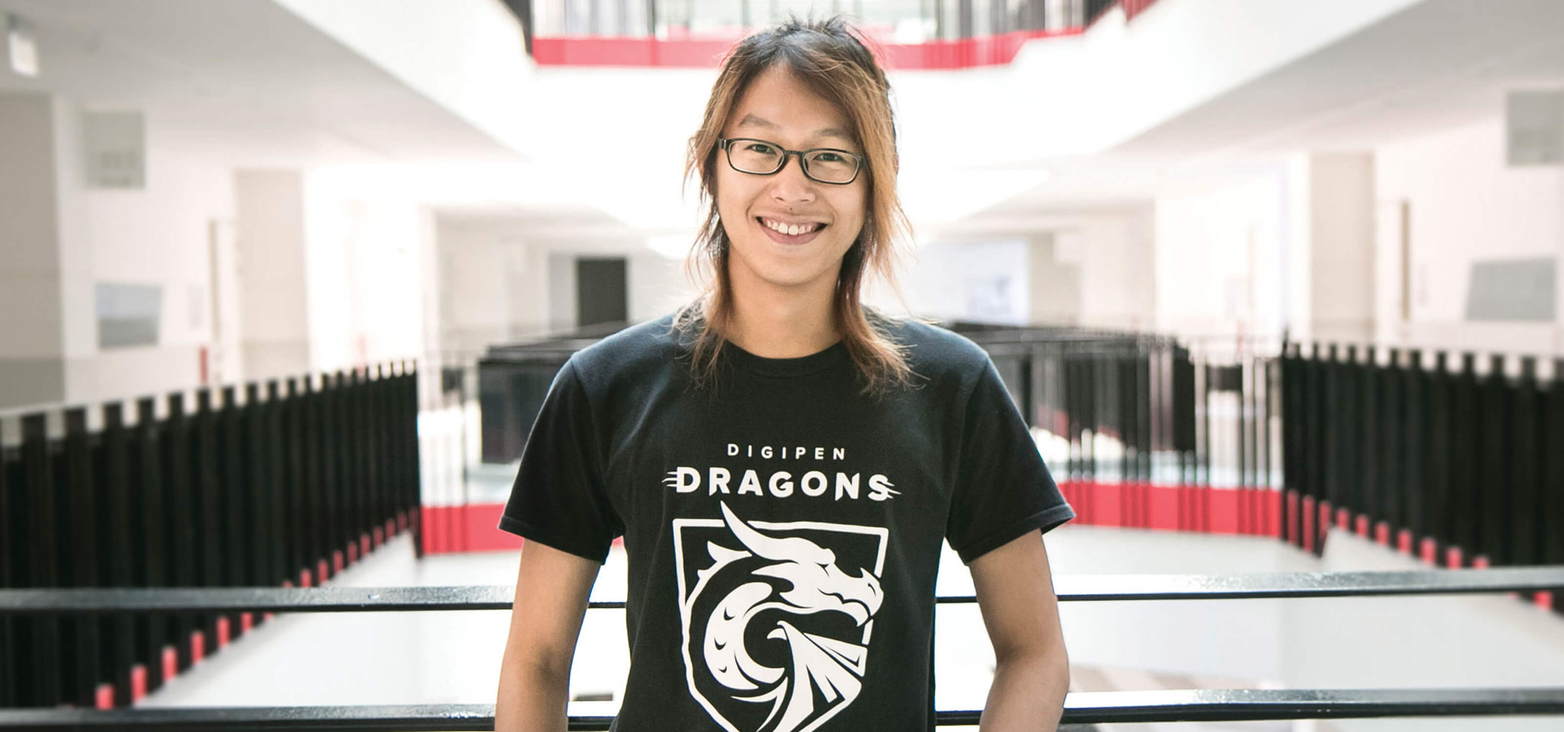 DigiPen graduate Jovi Kartolo poses for a photo at a railing on the second floor wearing a black DigiPen Dragons t-shirt