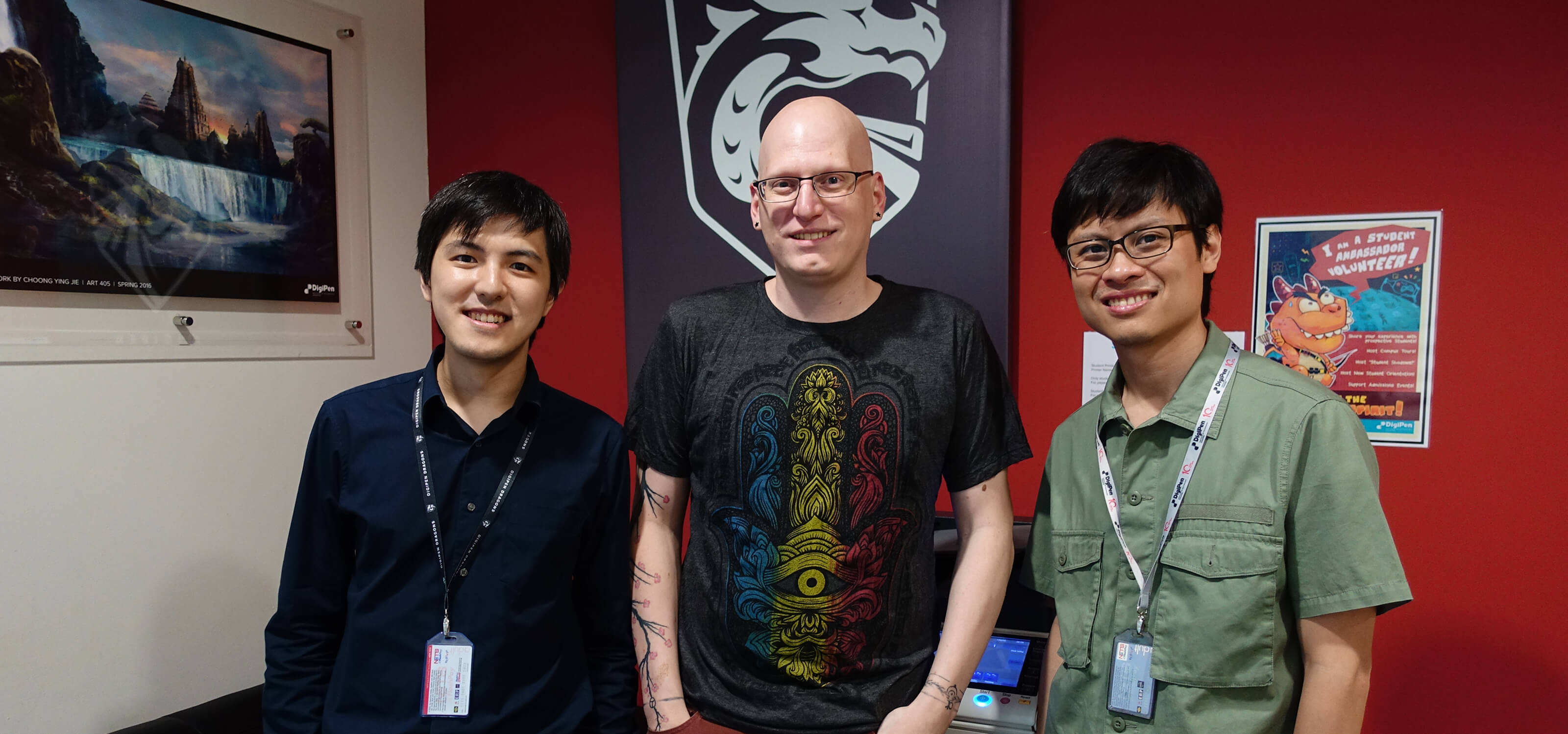 Howard Sin, Kevin Prior, and Gerald Wong pose smiling in an office on the DigiPen (Singapore) campus