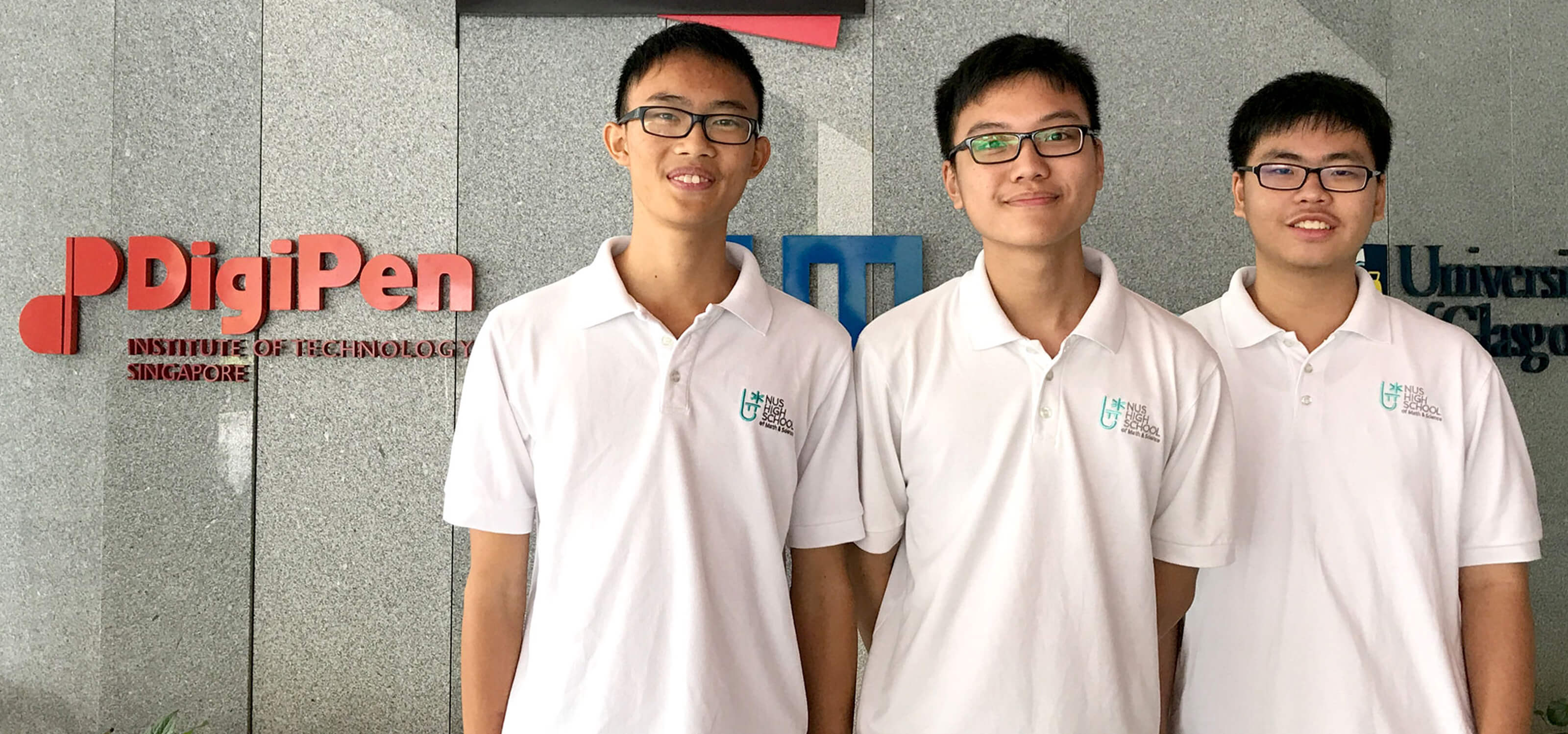 Three students from NUS High School pose for a photo in front of a gray marble wall with the SIT and DigiPen logos