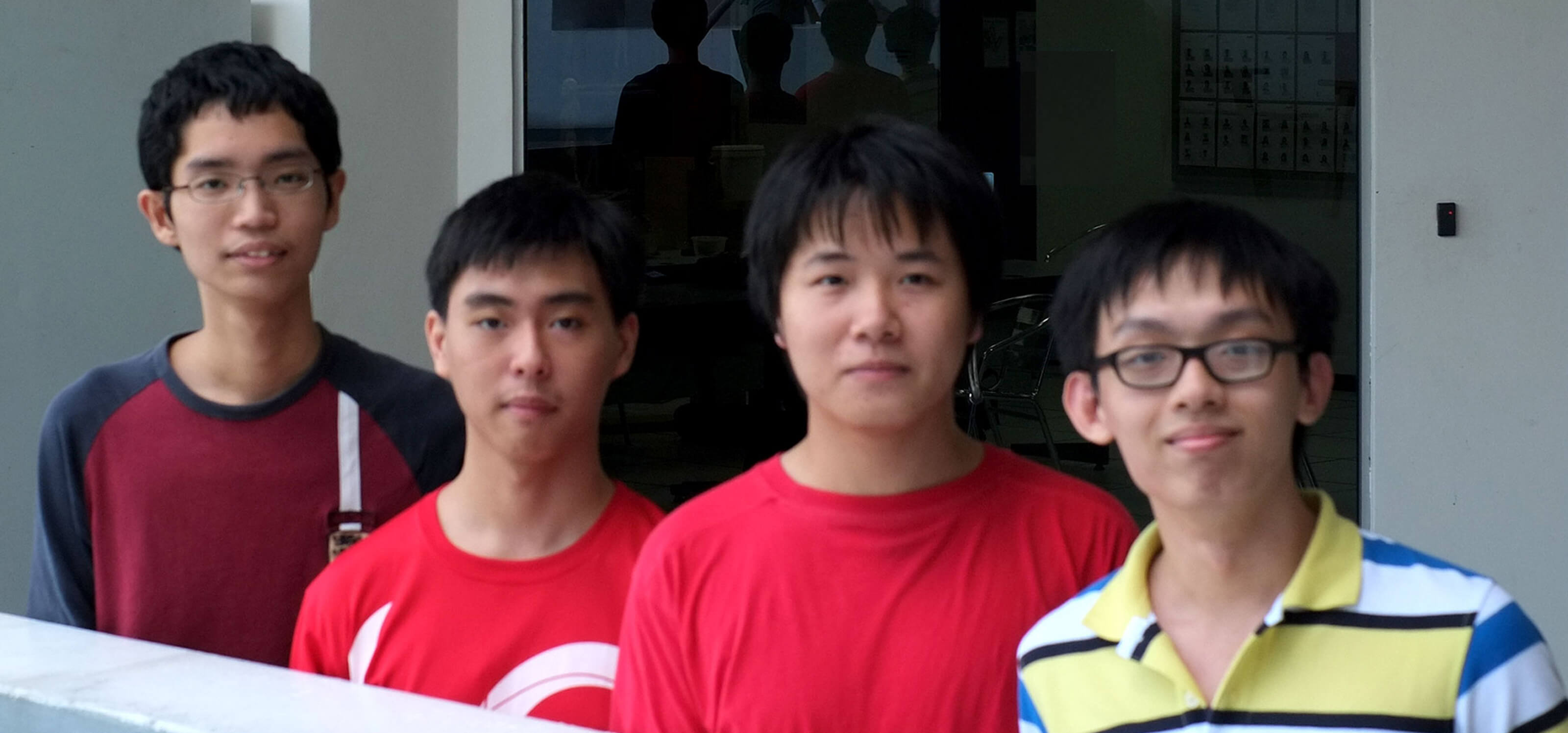 Four students pose for a photo behind a railing with an entrance to DigiPen (Singapore) behind them