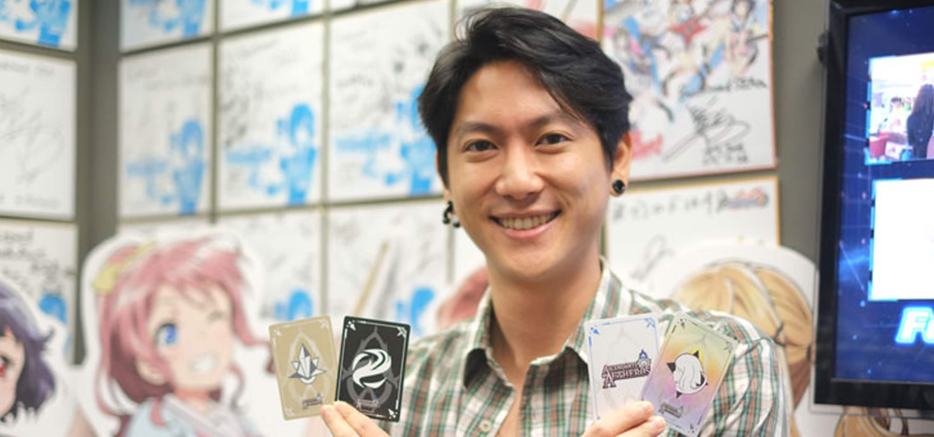 RTIS graduate Rudy Ng poses holding four cards from the card game Ascendants of Aetheros