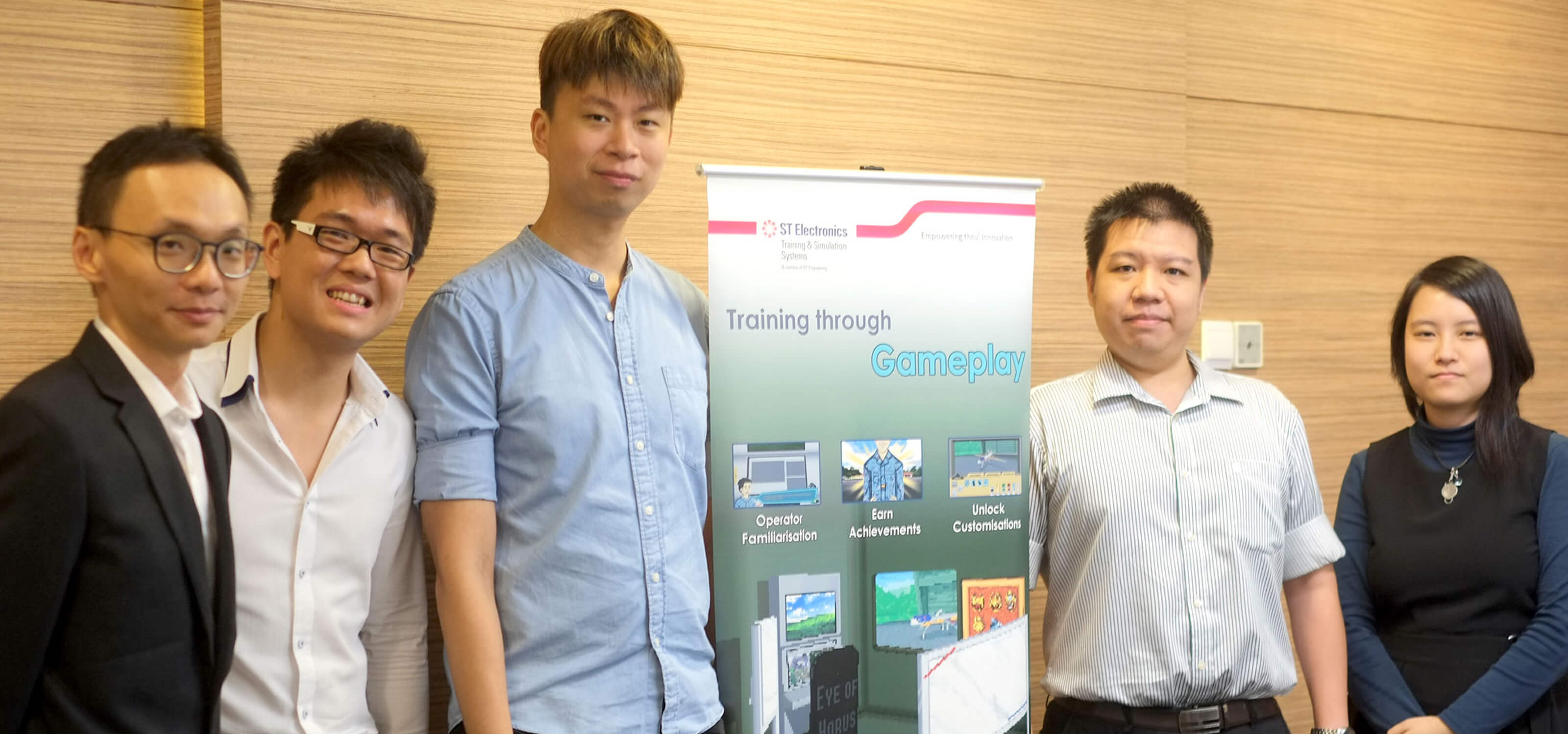 Team from ST Electronics poses for a photo with a vertical banner explaining a learning initiative using gameplay mechanics