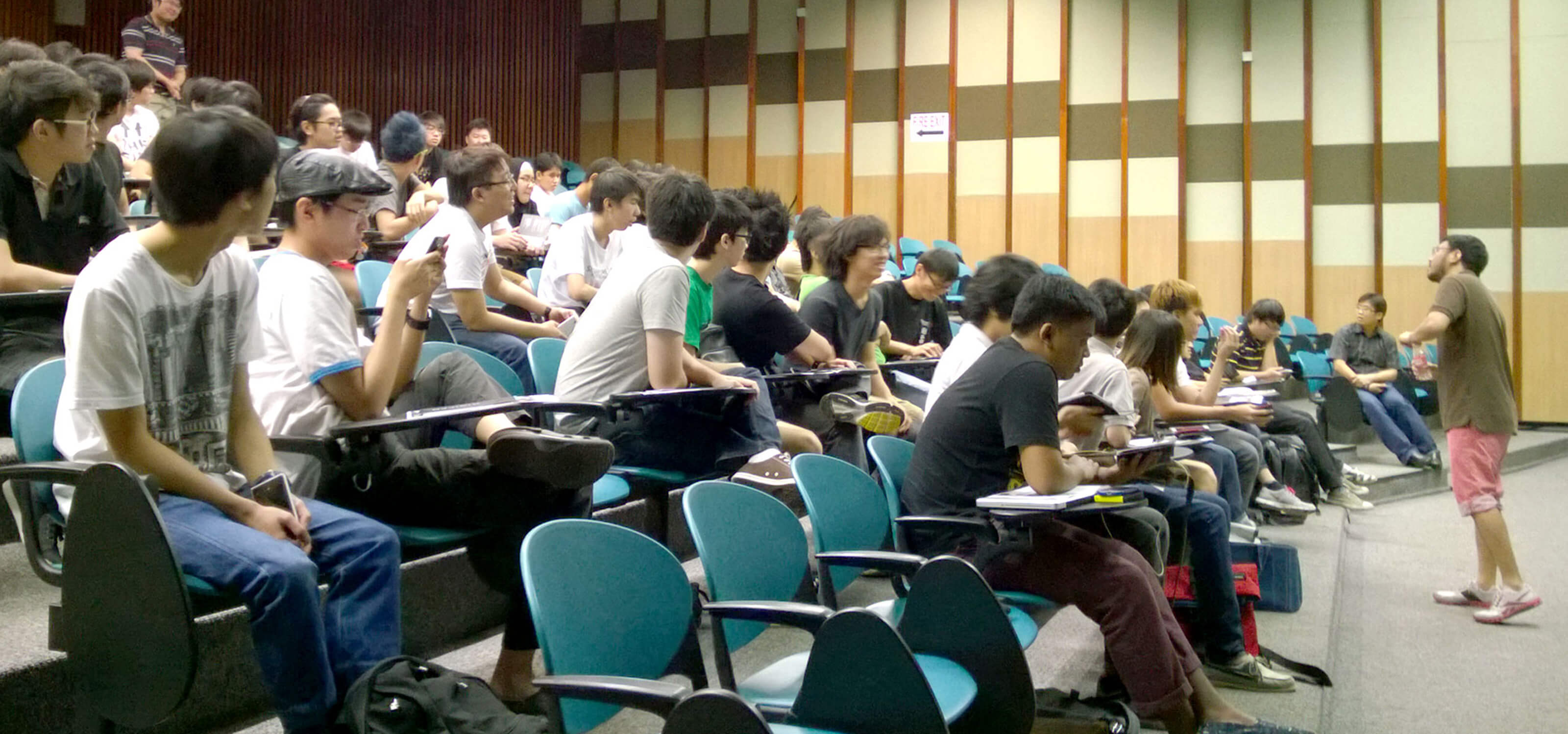 Dozens of polytechnic students attend a master class in an auditorium at DigiPen (Singapore)