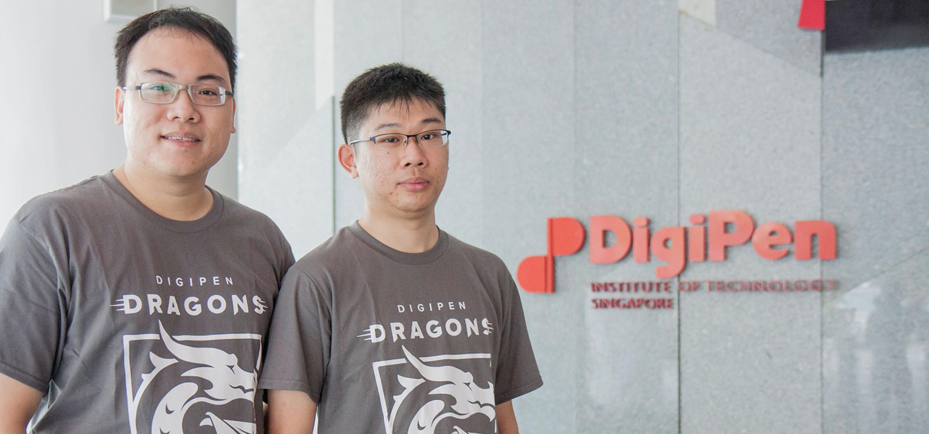 Graduates Tan Tien Wei Keith and Yap Teng Hong pose for a photo in gray DigiPen Dragons t-shirts next to the DigiPen building