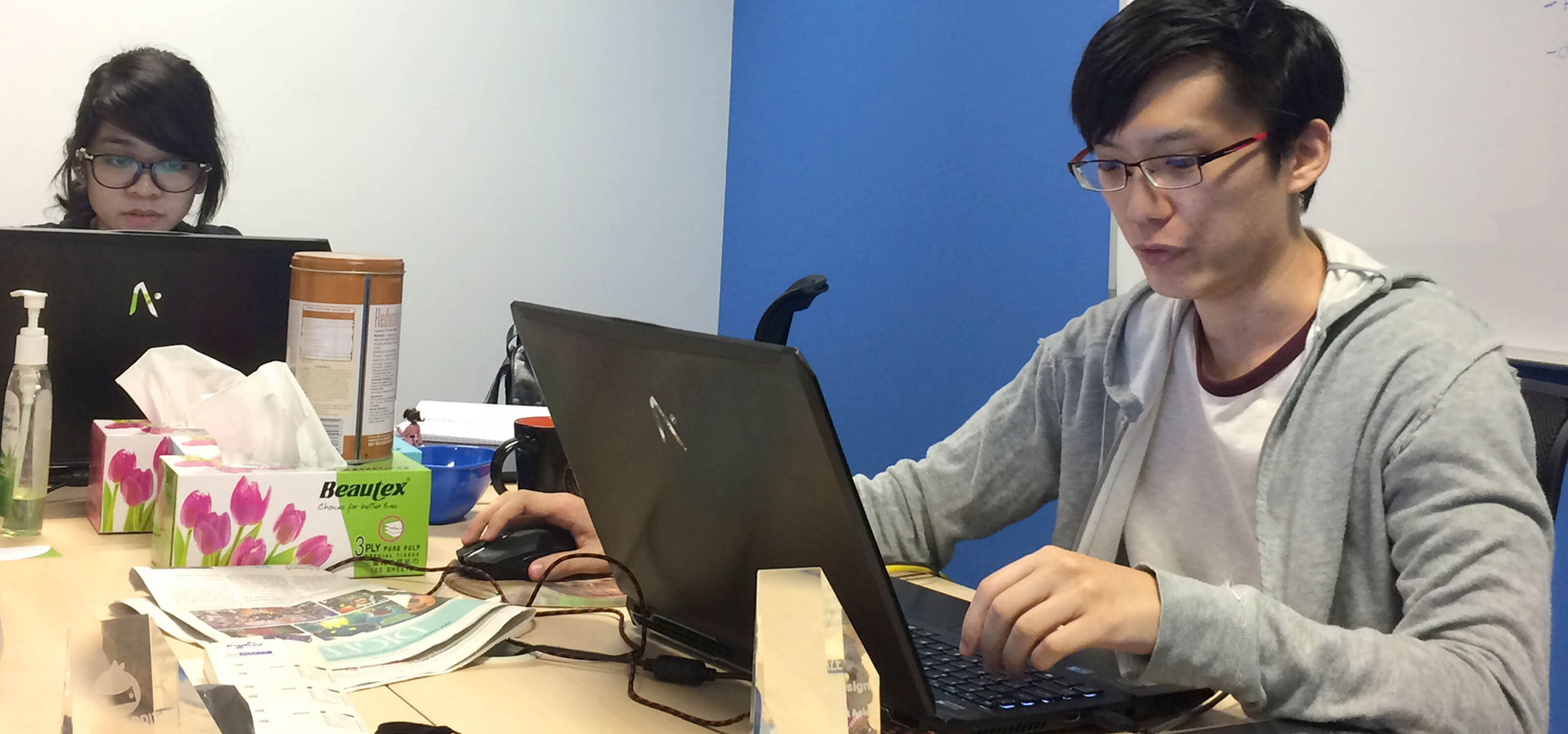 Alumnus Desmond Wong sits at a desk with a laptop computer surrounded by trinkets and awards