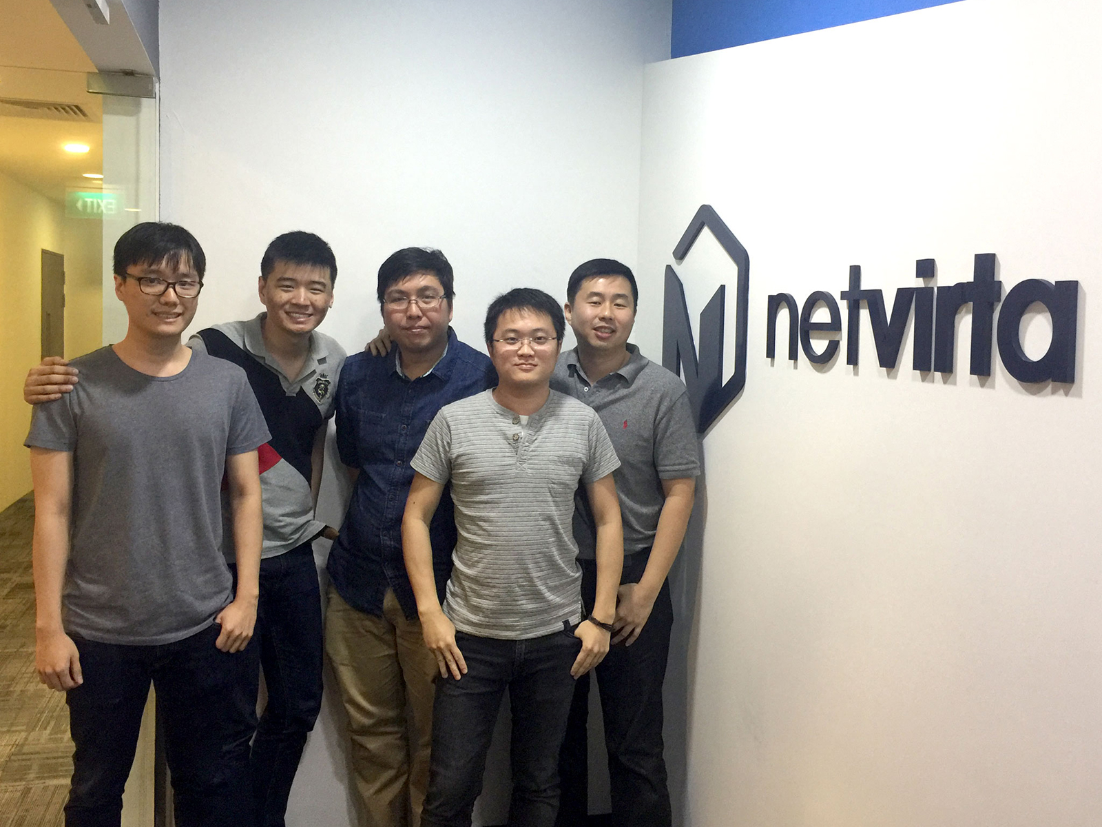 A group of DigiPen Singapore alumni pose next to the logo of Boston-based startup company NetVirta
