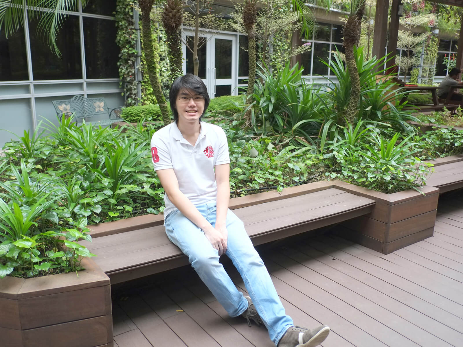 DigiPen graduate Cheng Ding Xiang poses for a photo sitting at a bench in an atrium area full of plants and trees