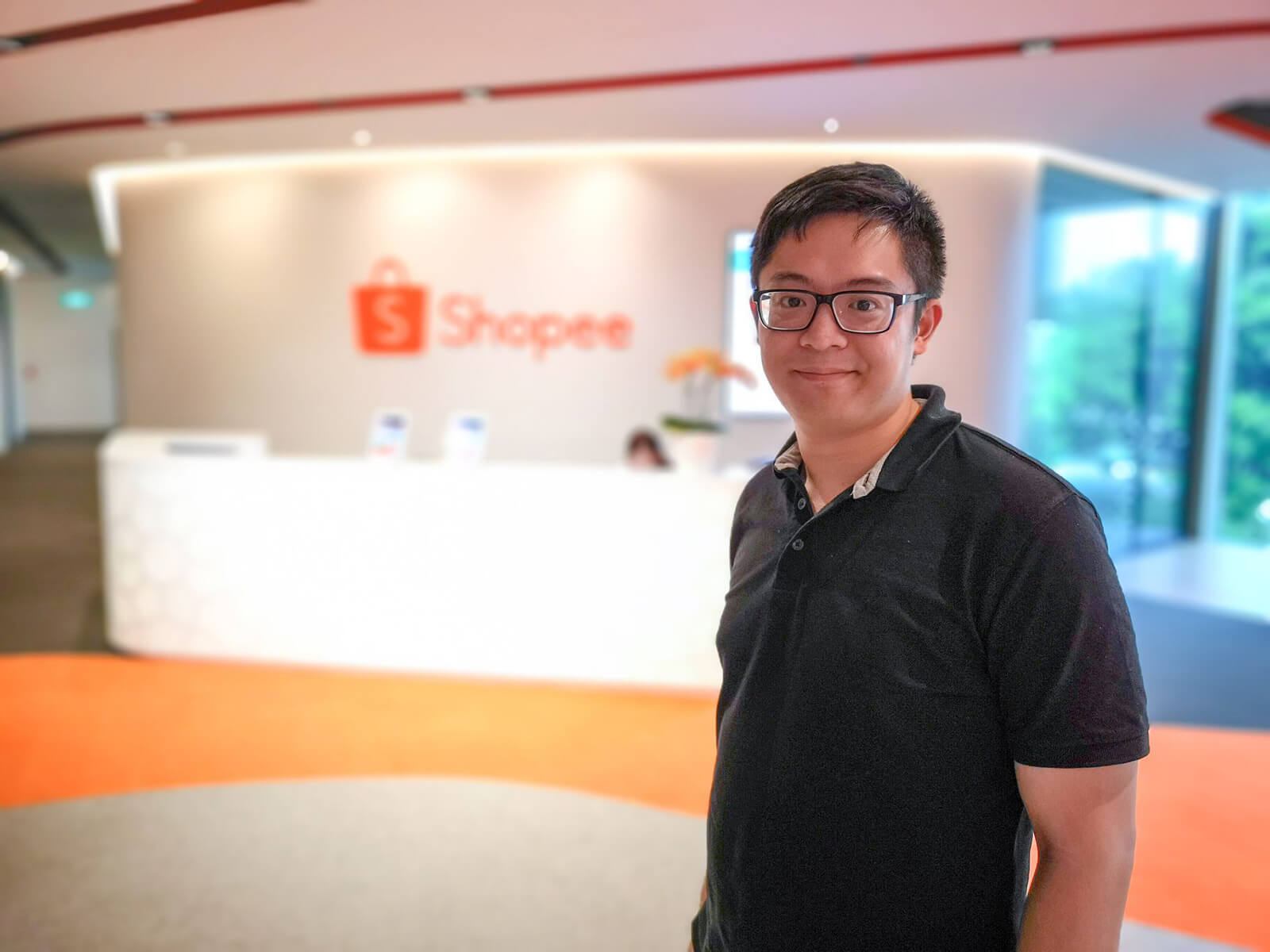DigiPen (Singapore) alumnus Chester Liew stands in front of a wall adorned with the Shopee logo