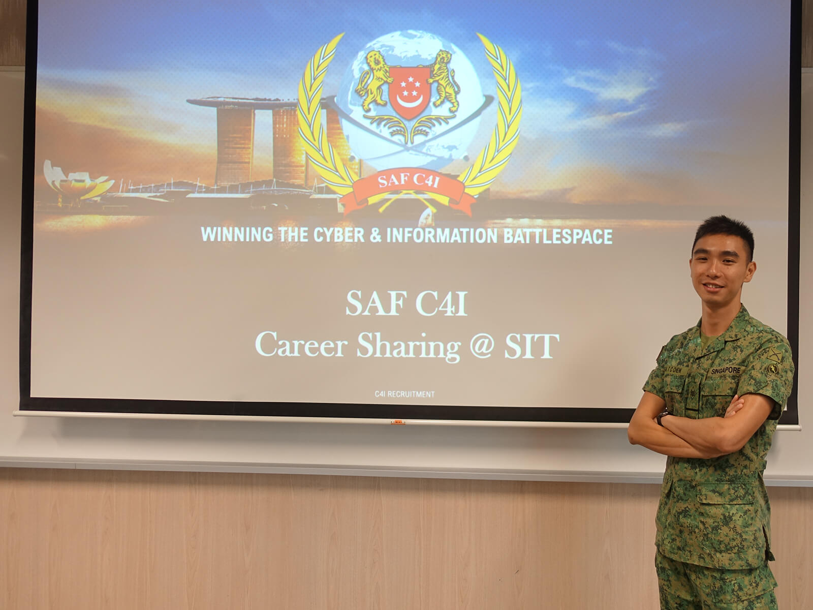 Chew Tee Chin stands in front of a projector screen with the SAF C4I logo.