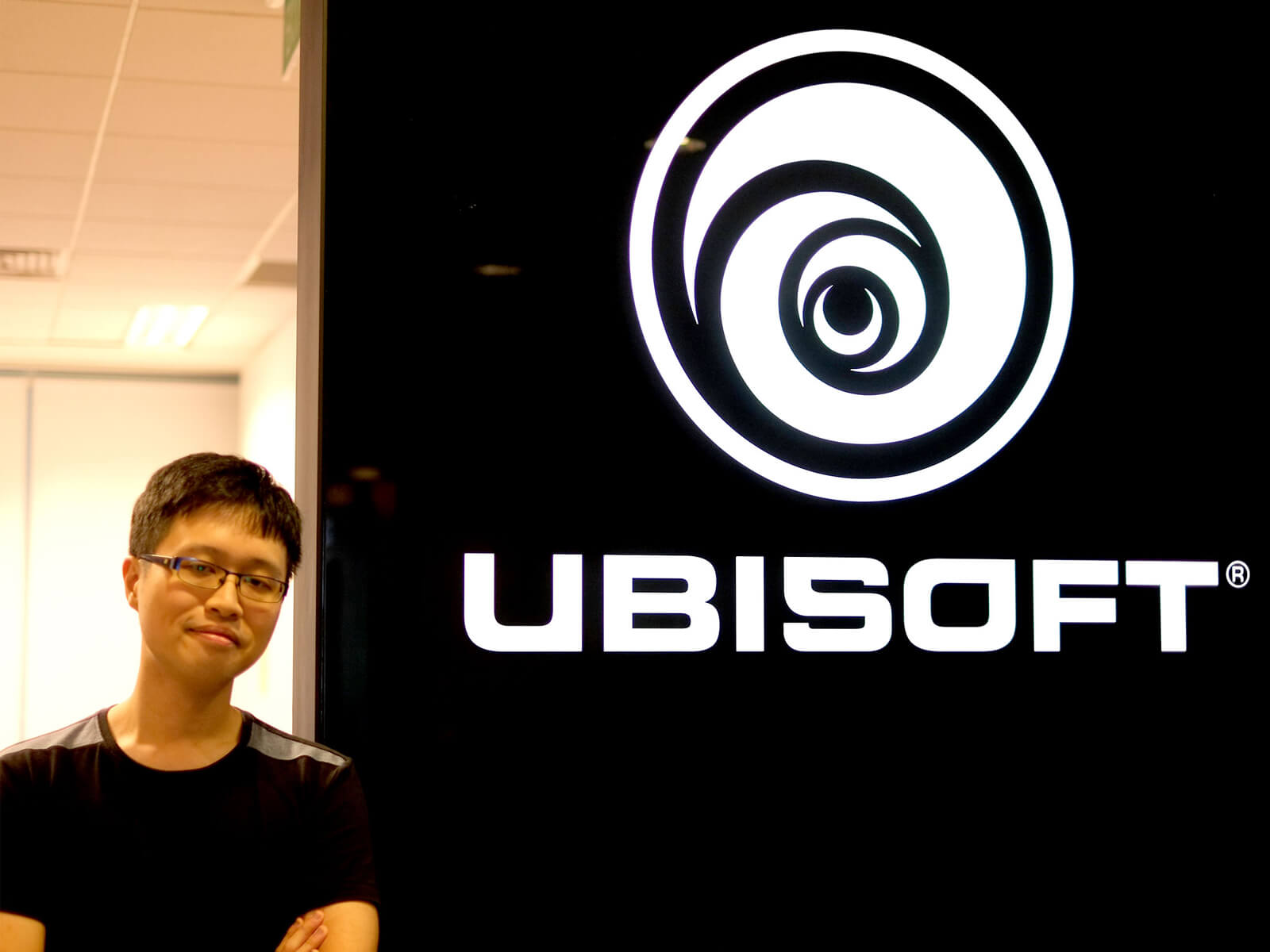 DigiPen graduate Chin Jia Hao stands with arms crossed next to black-and-white Ubisoft logo