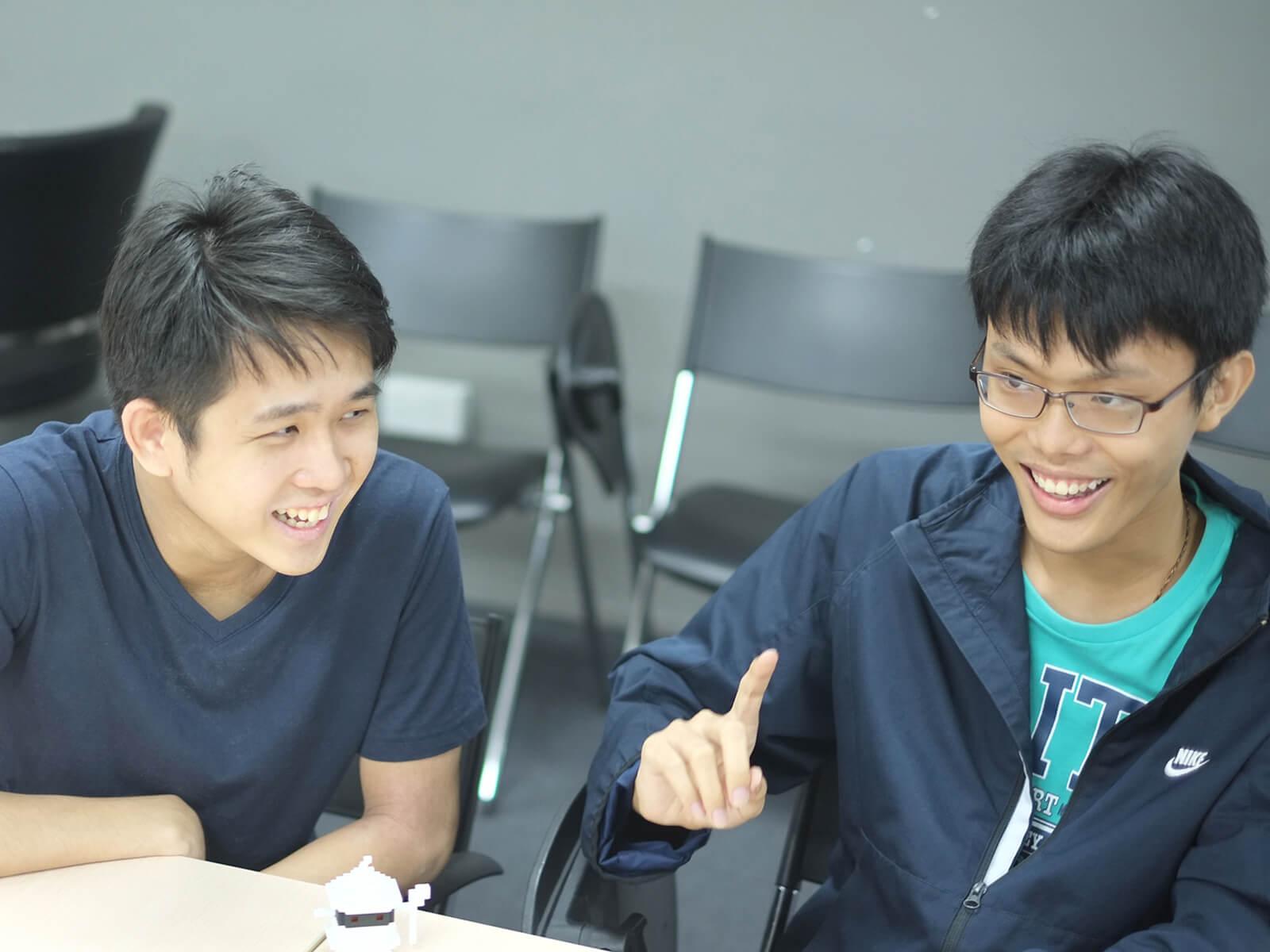 Graduates Chin Yong Kian and Lim Chian Song sit at a desk laughing