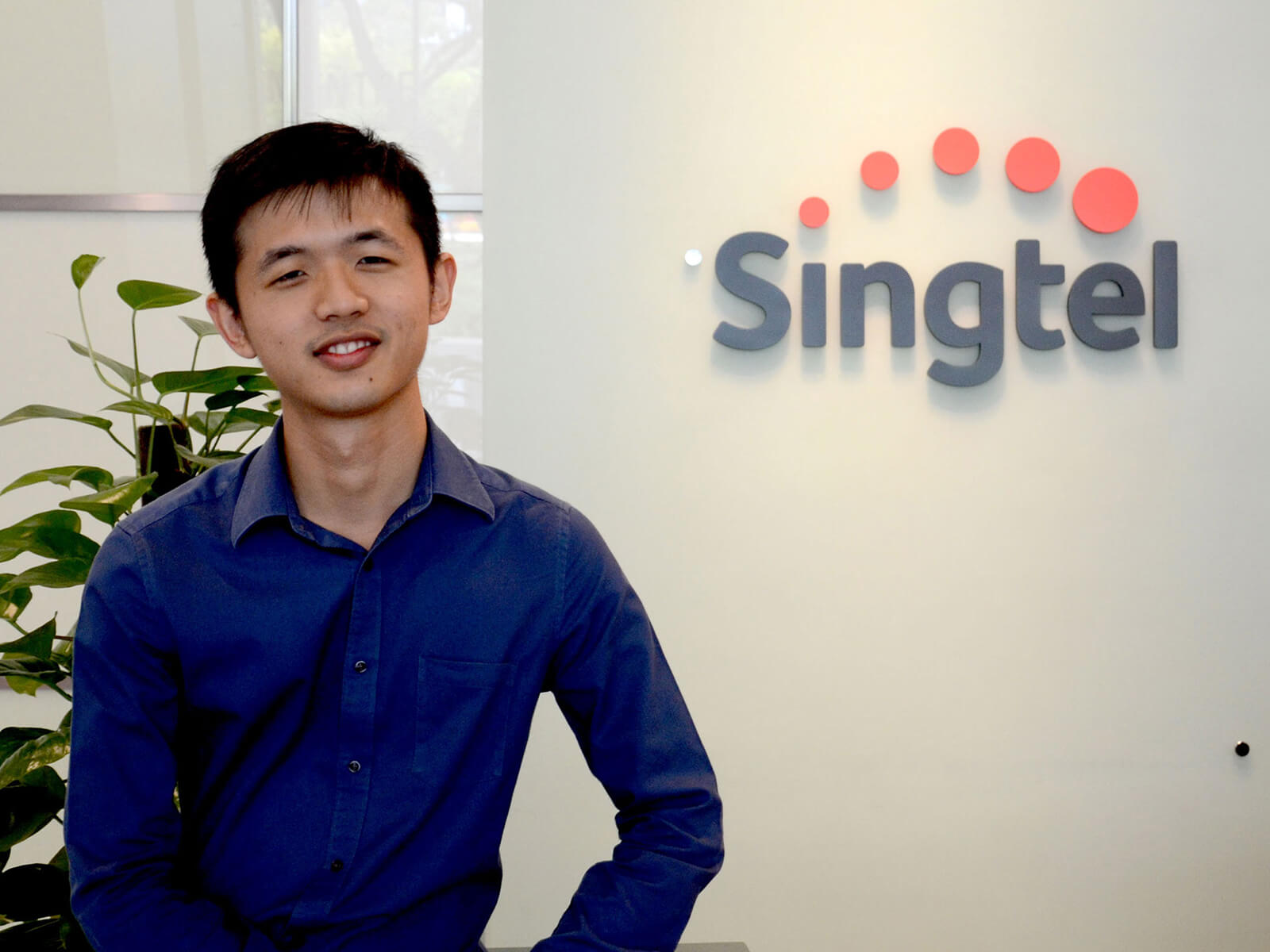 DigiPen (Singapore) BA in Game Design alumnus Daryl Bong poses in front of the Singtel logo