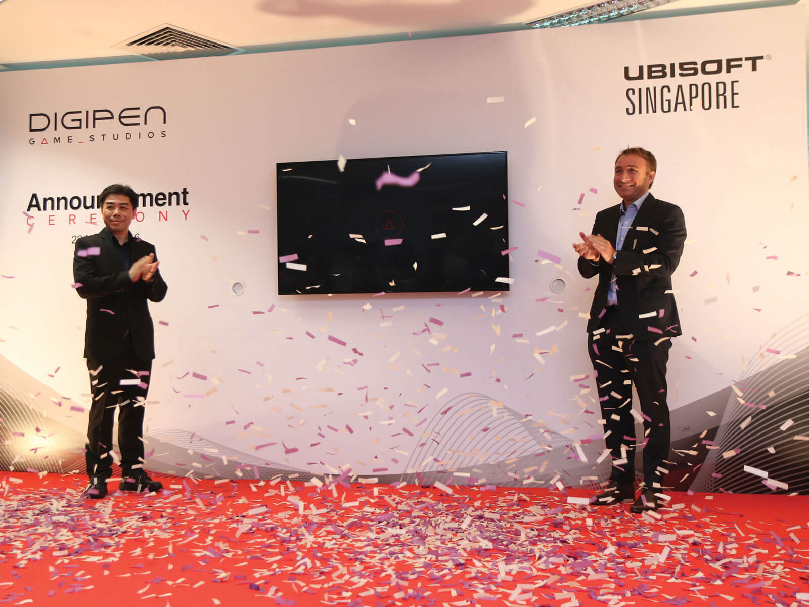 Jason Chu and Olivier de Rotalier applaud on stage as purple and white confetti falls. DigiPen and Ubisoft logos are on a wall behind them