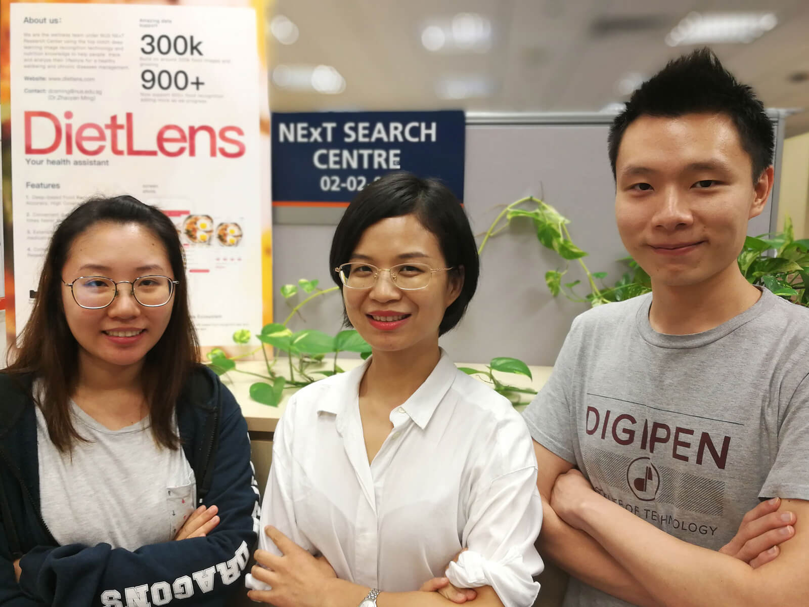 DigiPen (Singapore) alumni Irene Tan and Lim Sing Gee pose with a coworker in front of a DietLens banner