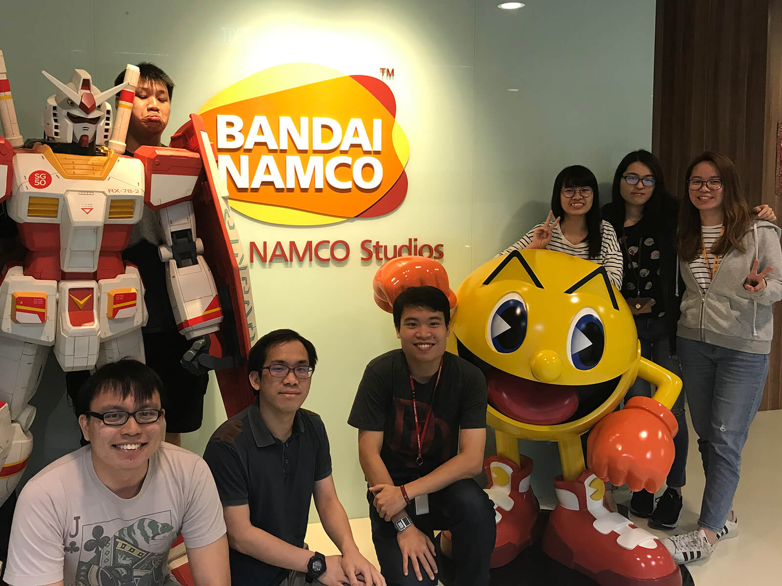 Group photo of eight DigiPen alumni in the lobby of Bandai Namco studio, posing by statues of Pac-Man and a mecha robot.