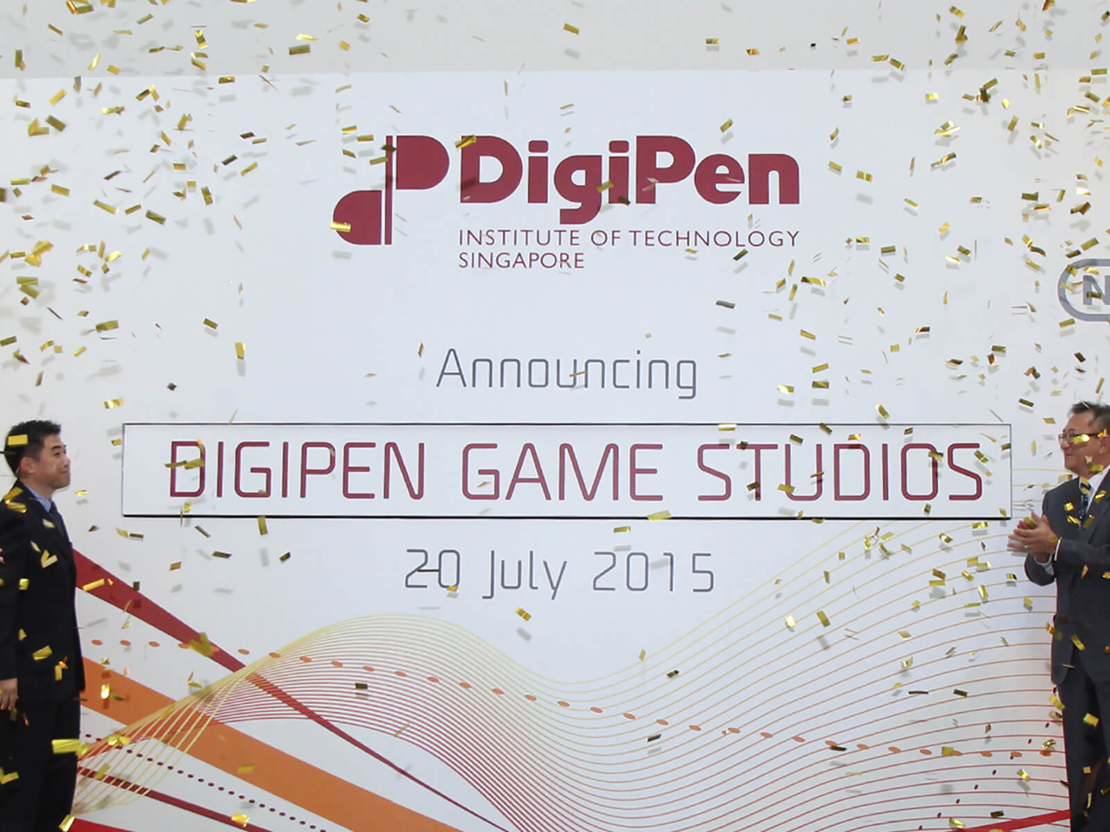 Representatives of DigiPen applaud the unveiling of the DigiPen Game Studios onstage as gold confetti falls from above