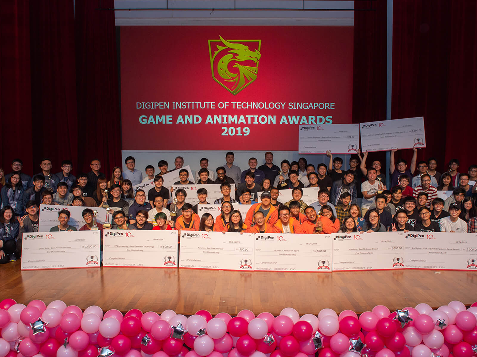 Four rows of students line up on stage to display their giant prize checks during the 2019 DigiPen Game and Animation Awards ceremony.