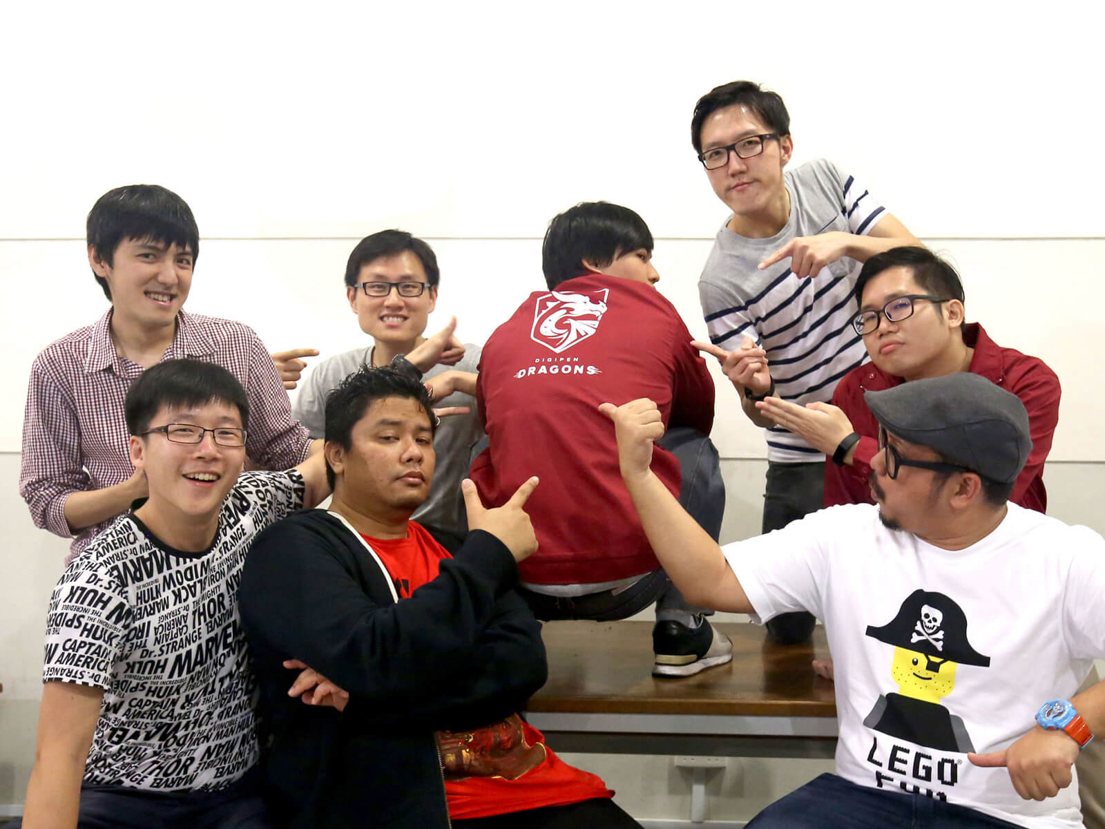 Members of the alumni committee point to the back of another member squatting on a desk who is wearing a red DigiPen shirt